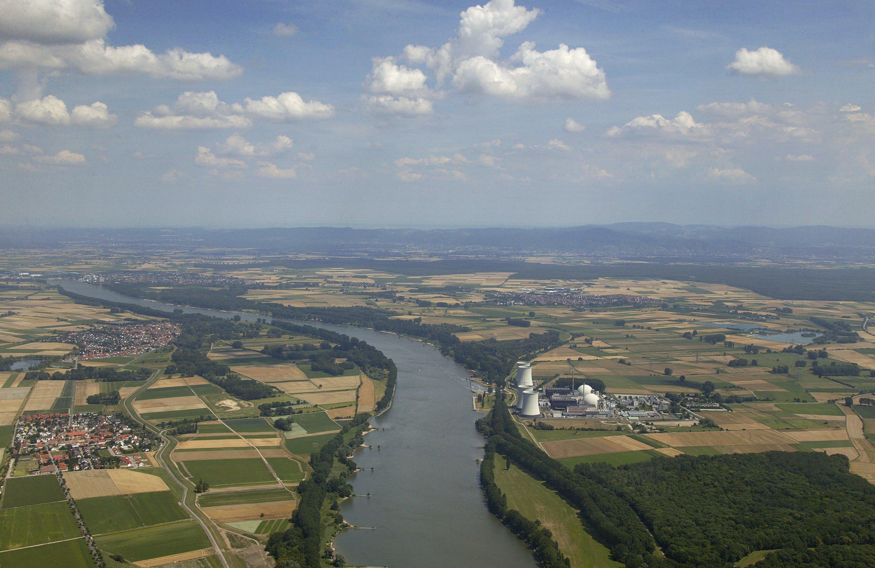 Luftaufnahme: Fluss Rhein fließt im weiten Bogen durch Landschaft mit gelben und grünen Feldern, am rechten Ufer Atomkraftwerk Biblis, am Horizont Mittelgebirge Odenwald, blauer dunstiger  Himmel mit Wolken