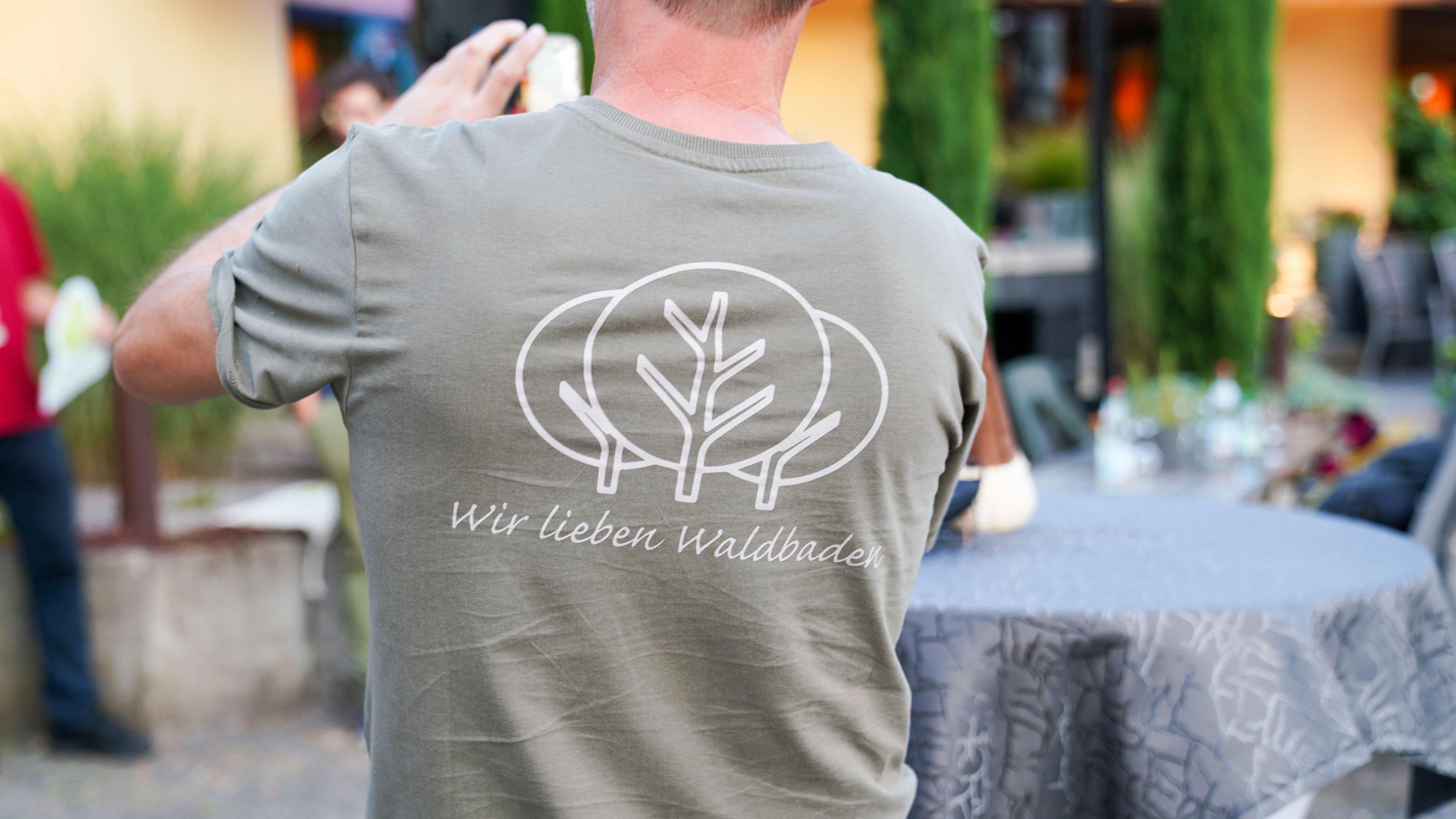 """Mann mit T-Shirt, auf dem """"Wir lieben Waldbaden"""" geschrieben steht."""