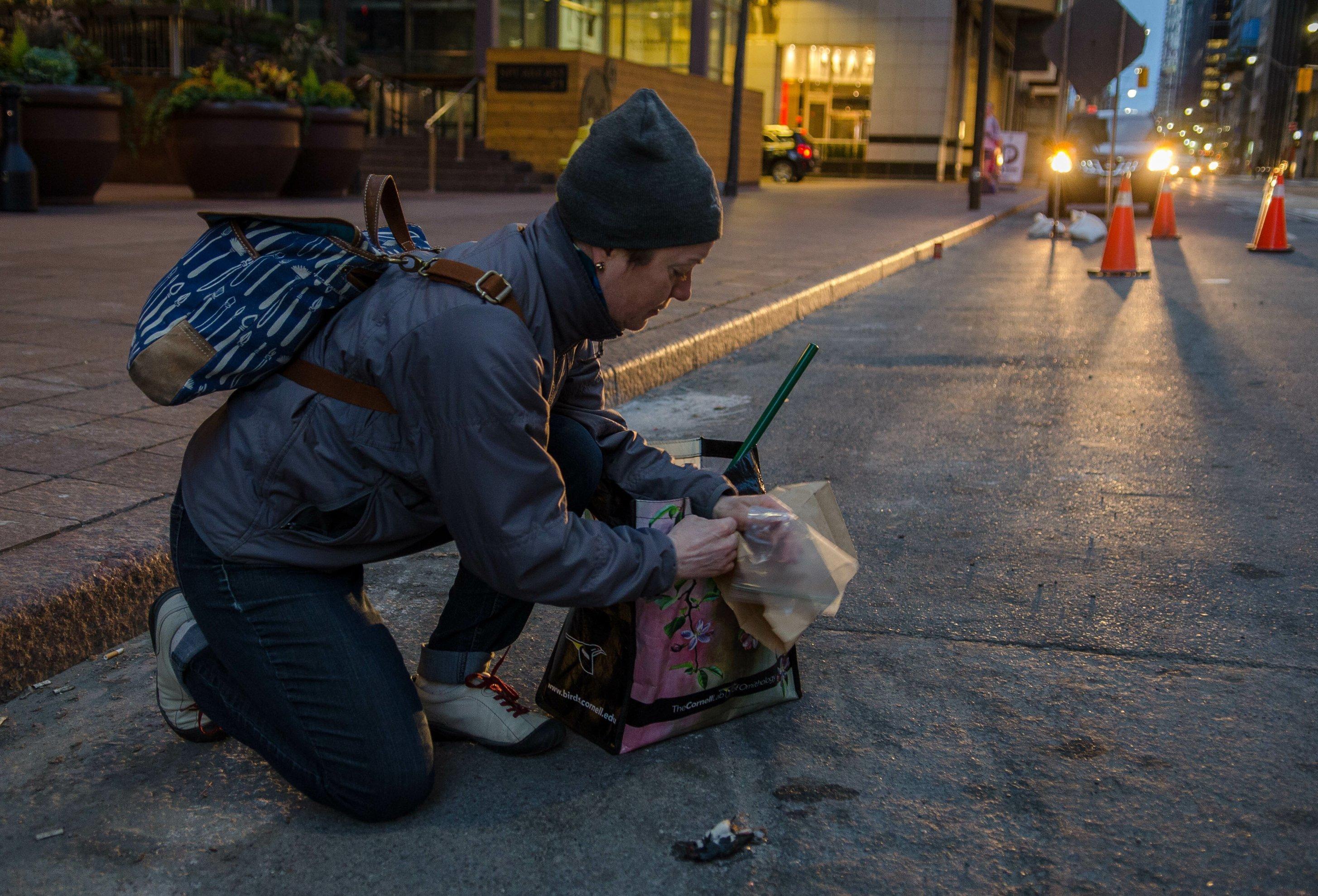 Eine Frau kniet auf der Straße, in der Hand ein Papier, in das sie den toten Vogel neben sich einhüllen und wegbringen wird