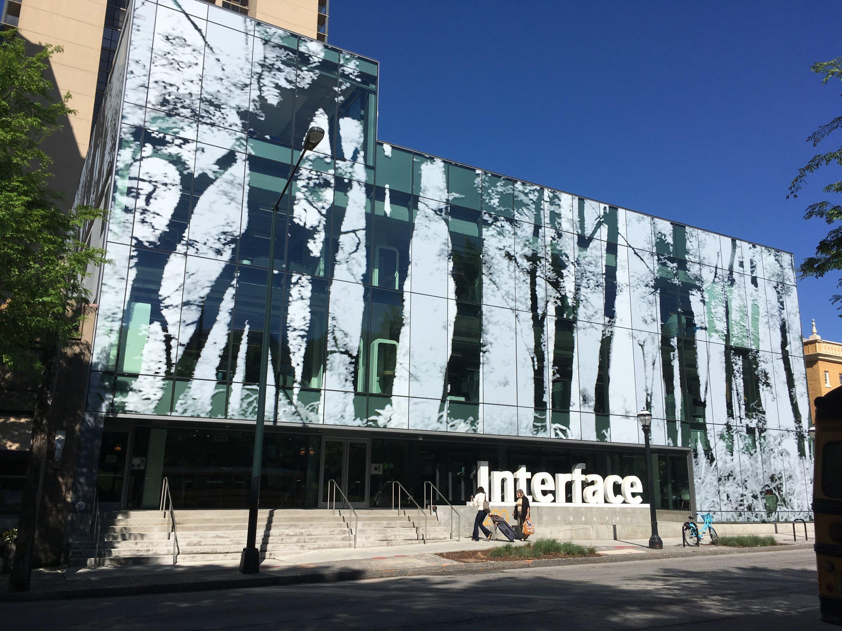 Auf der Fassade ist die naturgetreue, überdimensionierte Abbildung eines Waldstücks zu sehen