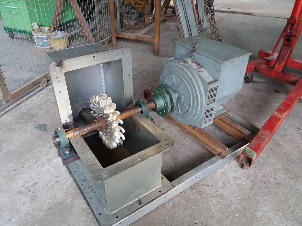 Da Foto zeigt ein Schaufelrad auf der Welle eines Generator in einem noch geöffneten grauen Kasten. –  … Der Rotor wird dann im Gehäuse installiert und mit einer Stahlwelle mit dem Generator verbunden …