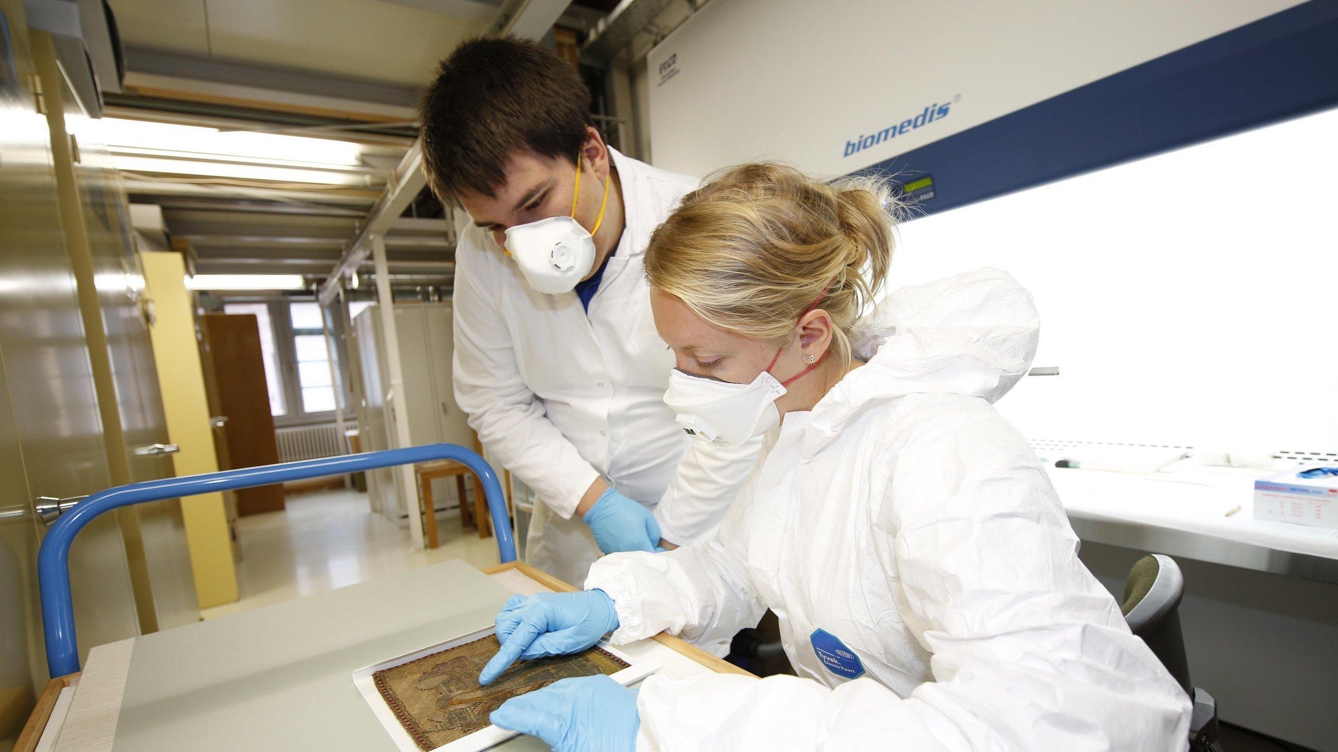 Ein Mann und eine Frau in weißer Schutzkleidung mit Atemmaske beugen sich über ein historisches Bild.