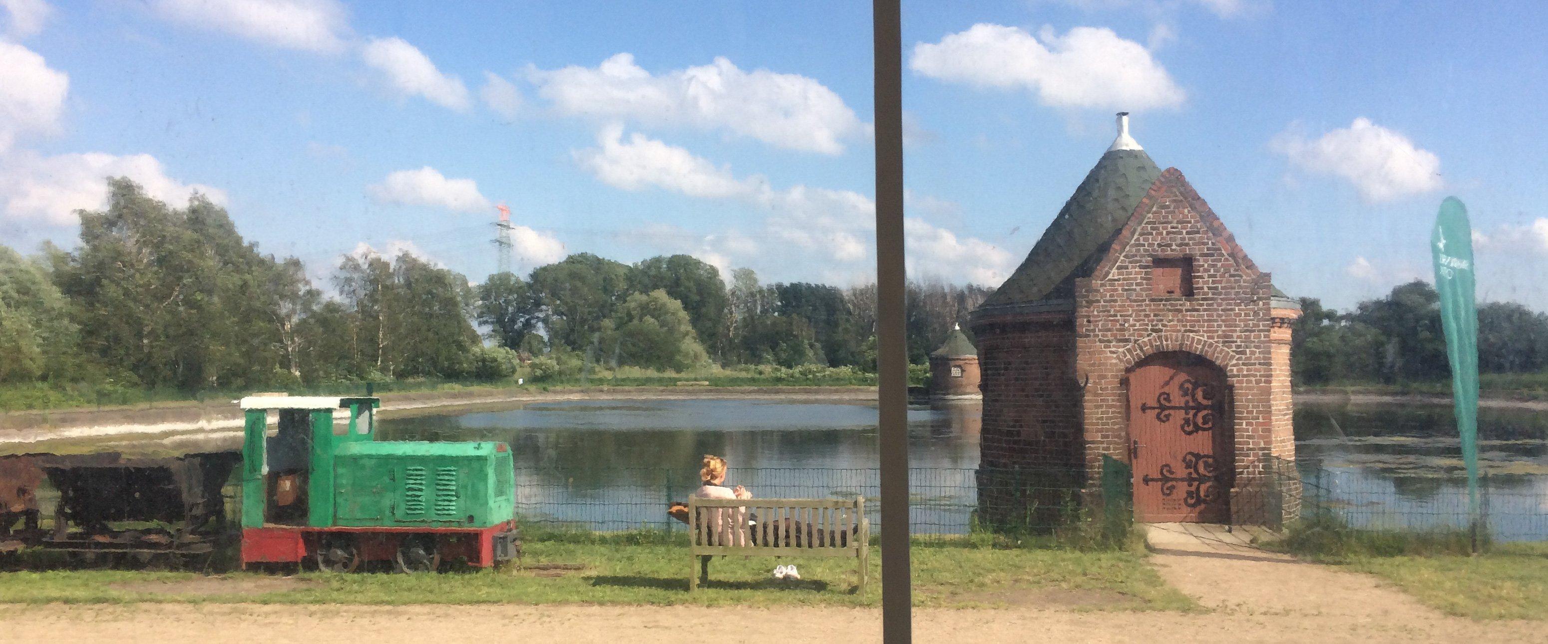 Blick über ein Wasserreservoir, davor ein Backsteinhäuschen und eine Grubenlokomotive. Ein Mensch sitzt auf einer Bank.