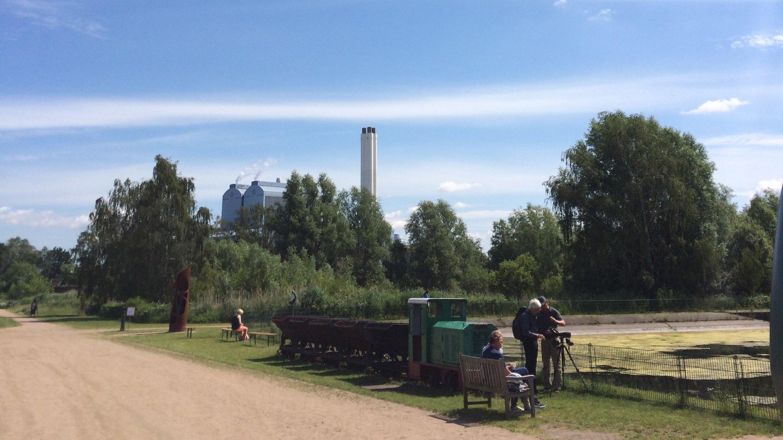Neben einem Wasserreservoir steht eine Grubenlok. Zwei Menschen schauen auf einen Prospekt. Im Hintergrund ragen der Schlot und Betriebsgebäude eines Kraftwerks über die Baumwipfel.