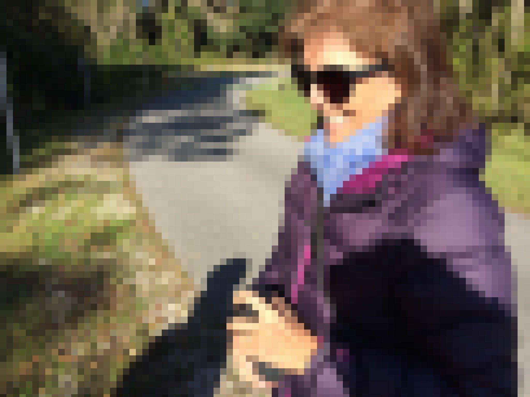Eine Frau mit Sonnenbrille, schulterlangem braunen Haar und einer Daunenjacke steht lächelnd in der Sonne. In der Hand hält sie einen kleinen schwarzen Lautsprecher.