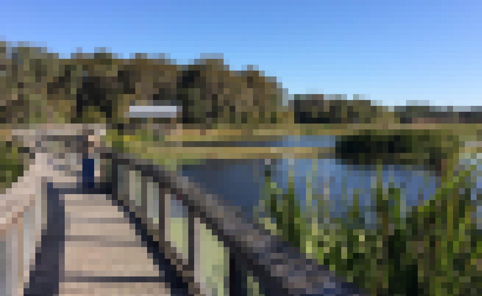 Auf einem Holzsteg steht ein Mann und zielt mit seinem Teleobjektiv auf Vögel, die von einem Teich aufsteigen. Im Hintergrund ein Unterstand, Wald, blauer Himmel.