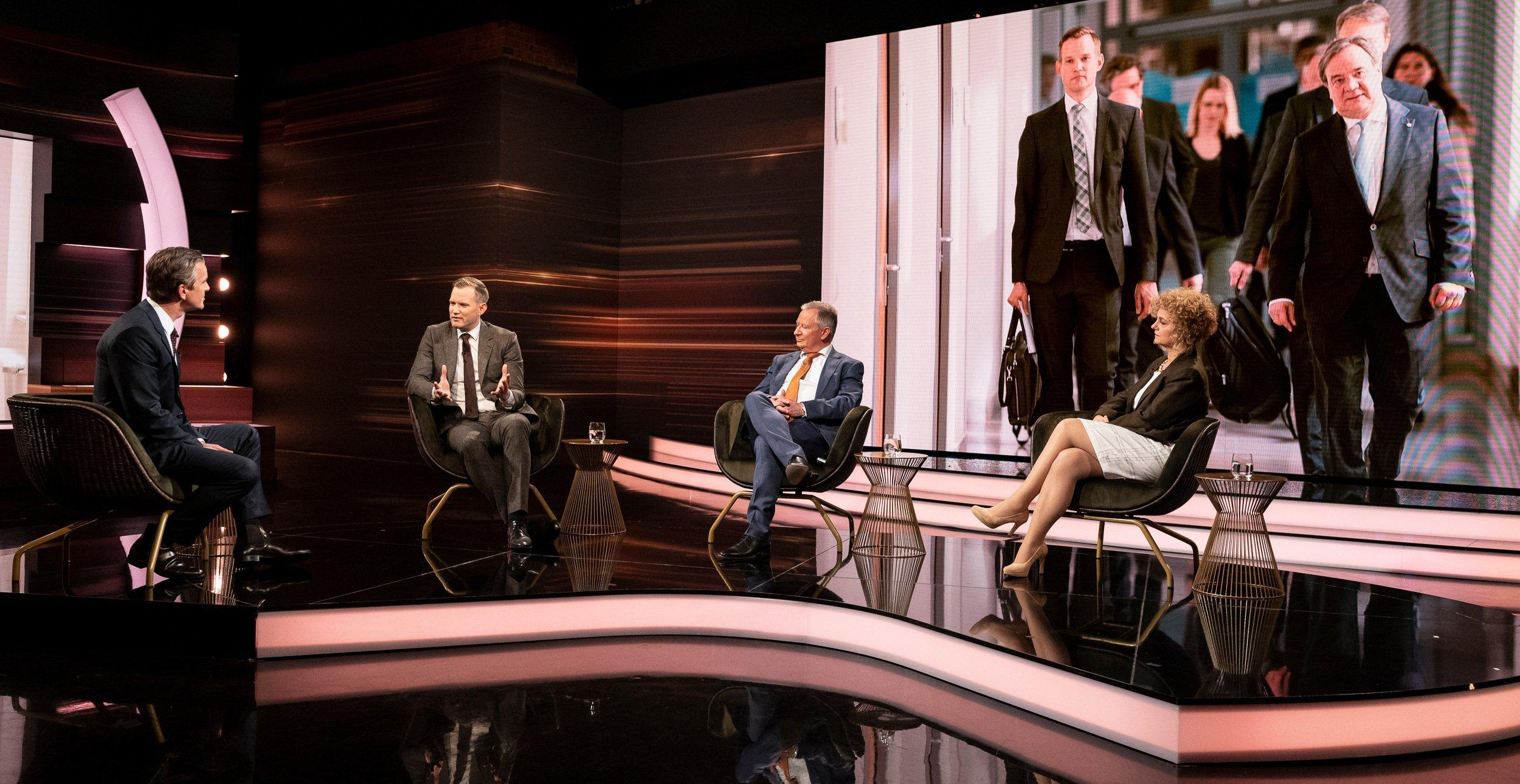 Drei Männer und eine Frau sitzen in einem in Brauntönen gehaltenen Fernsehstudio und sprechen miteinander. Im Hintergrund ein großes Foto, auf dem Menschen in Anzägen in Zweierreihen einen Korridor entlanggehen.