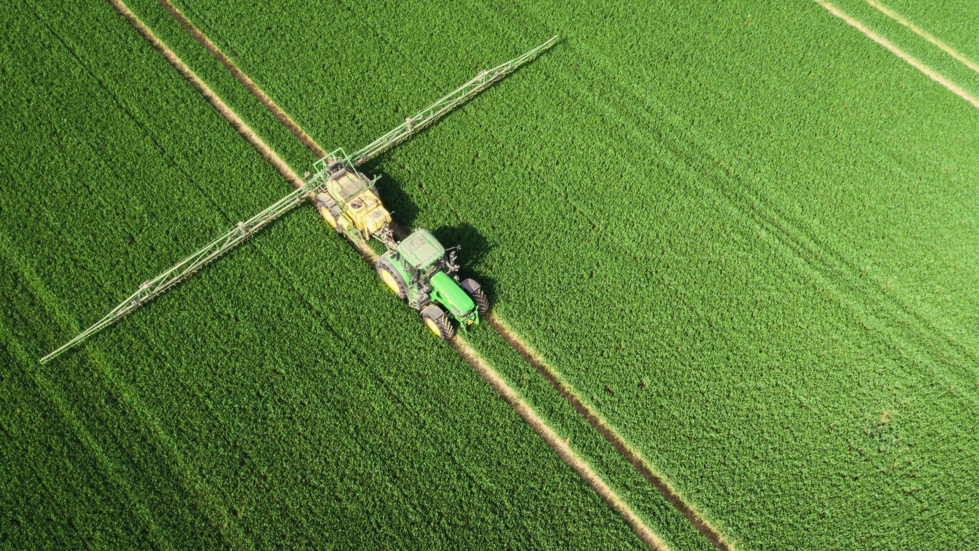 Luftbildaufnahme eines Traktors, der auf einem grünen Feld Dünger ausbringt. Copyright: © 2021Netflix, Inc.