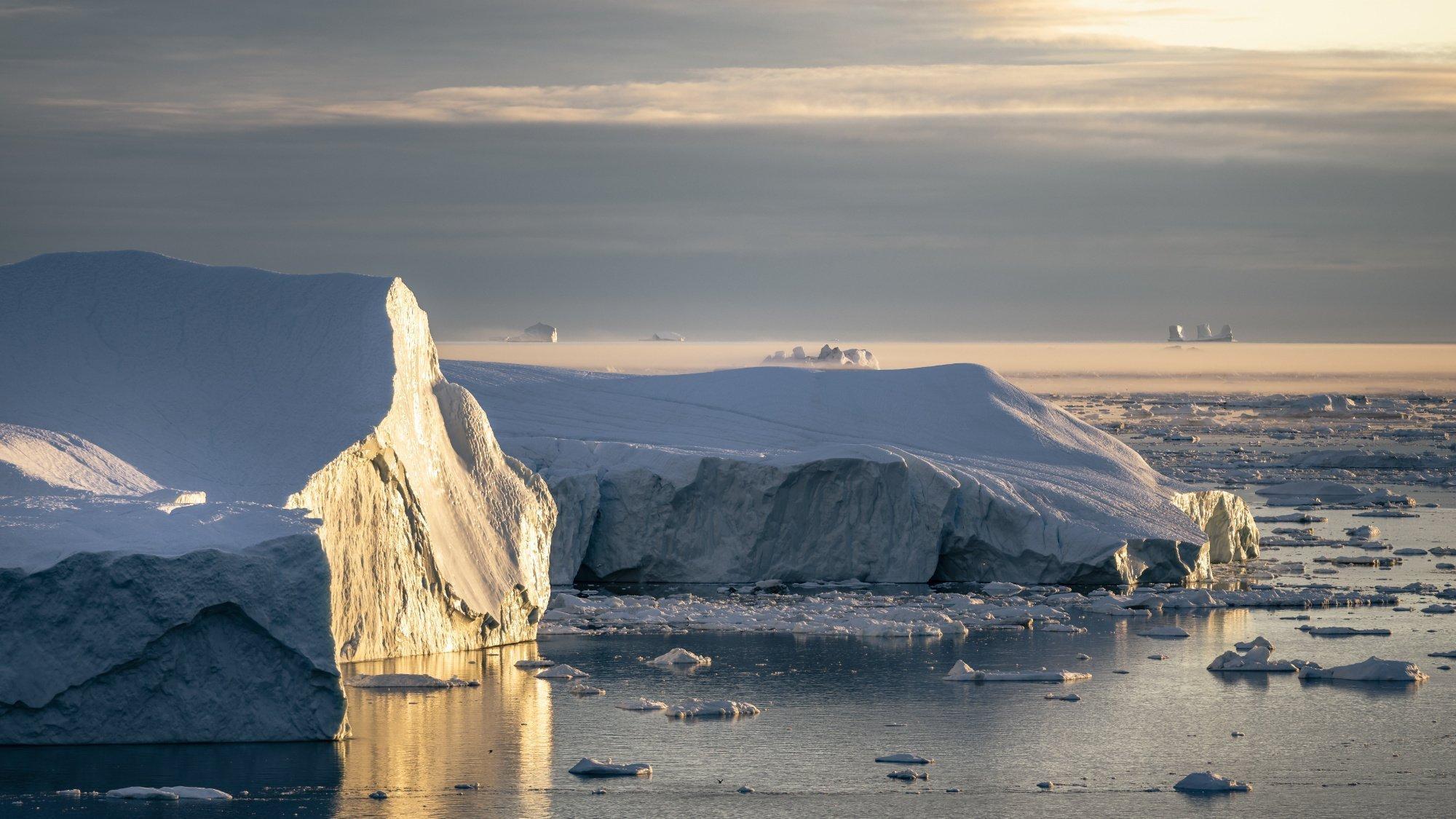 Auf dem Meer schwimmen Eisberge, die seitlich von der Sonne angeschienen werden. Rechte: Edward Felton, © 2021Netflix, Inc.