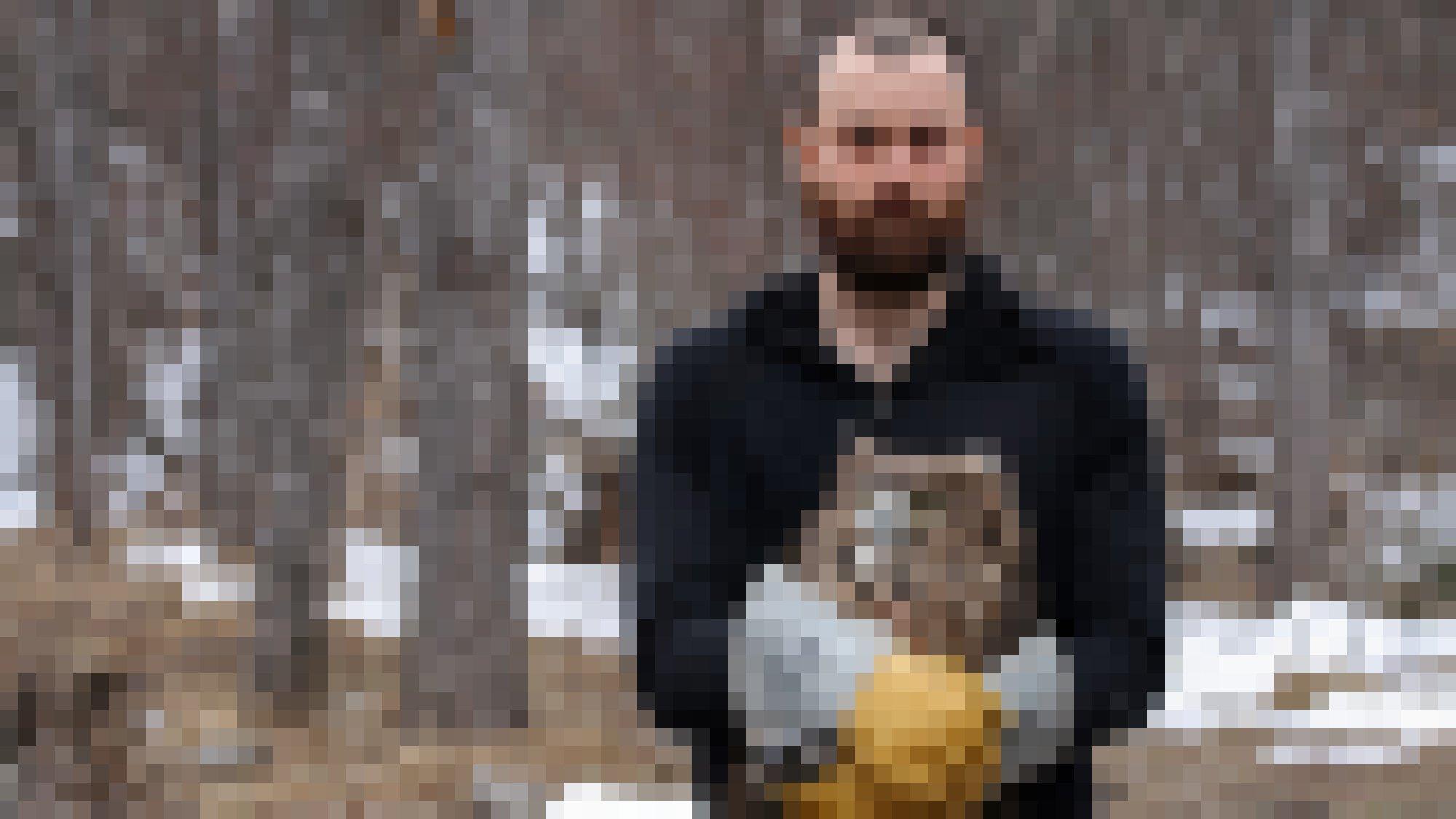 Ein Mann mit Bart und dicken Lederhandschuhen hält eine Eule in den Händen, die einen Fisch im Schnabel hat.