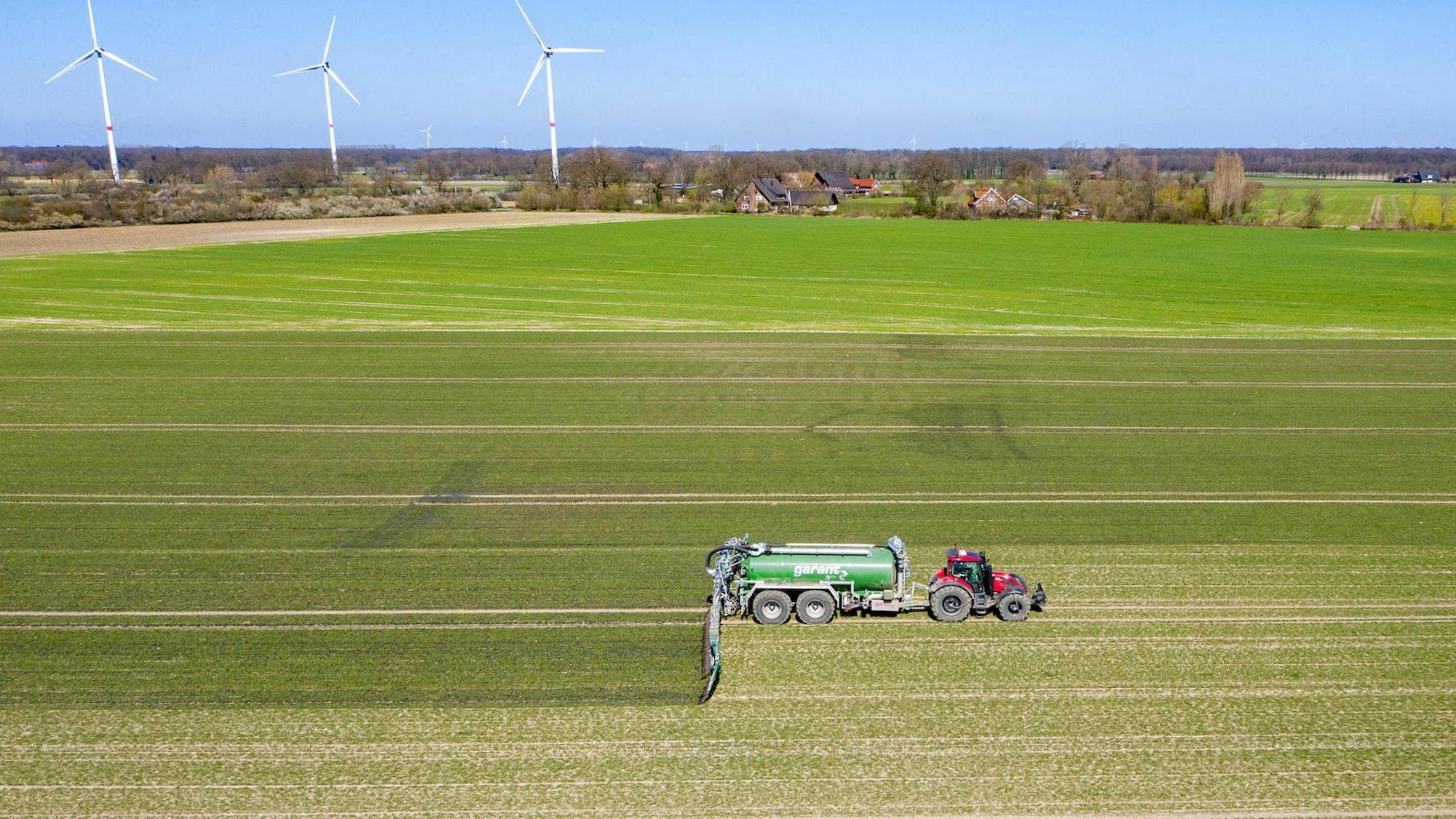 Luftaufnahme: Ein Trecker mit Güllefass bei der Ausbringung von Flüssigmist zur Düngung eines jungen Getreidebestandes im Frühjahr, im Hintergrund drei Windräder.