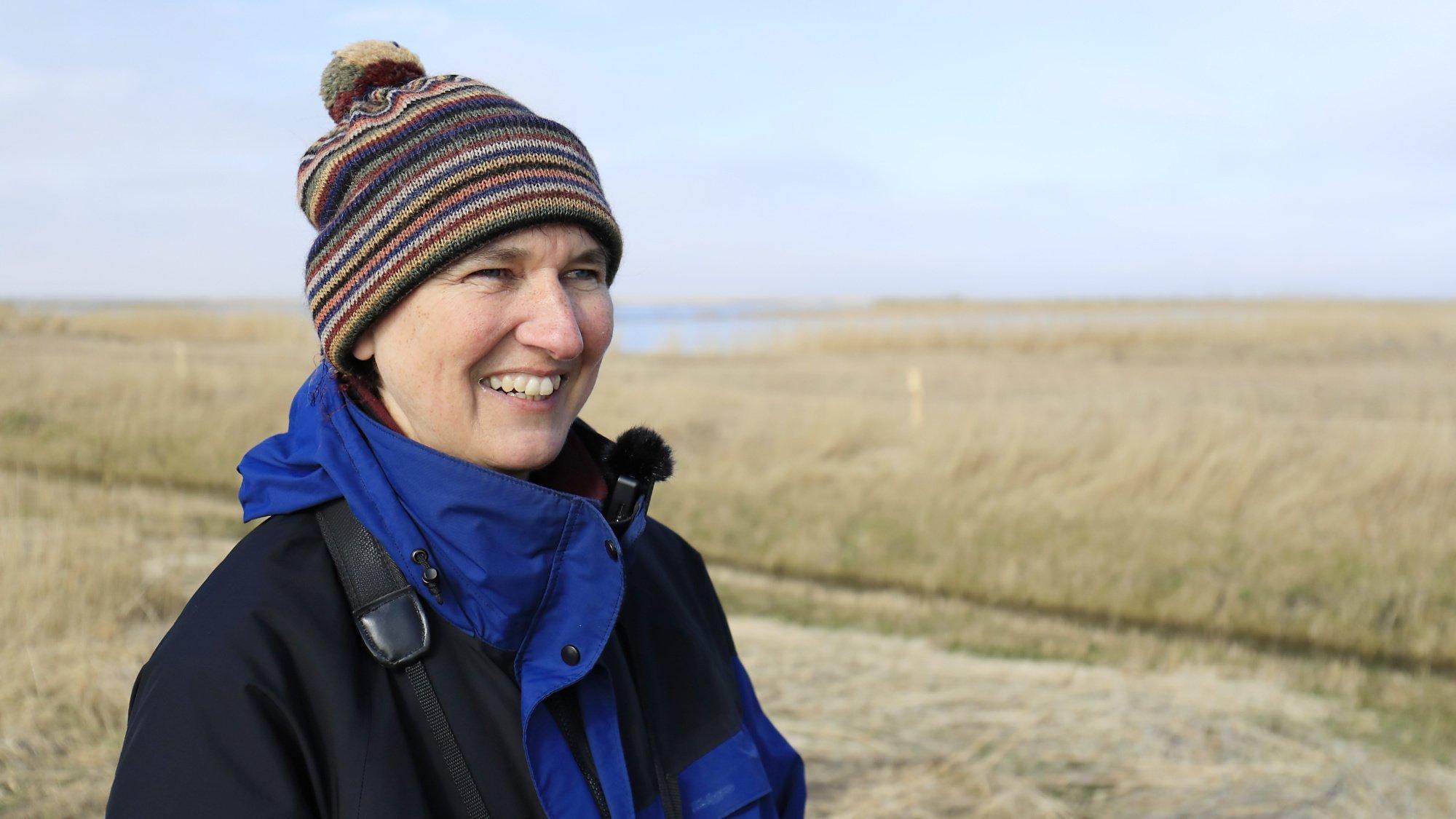 Barbara Ganter steht in blau-schwarzer Winterjacke und Mütze vor einer Graslandschaft.