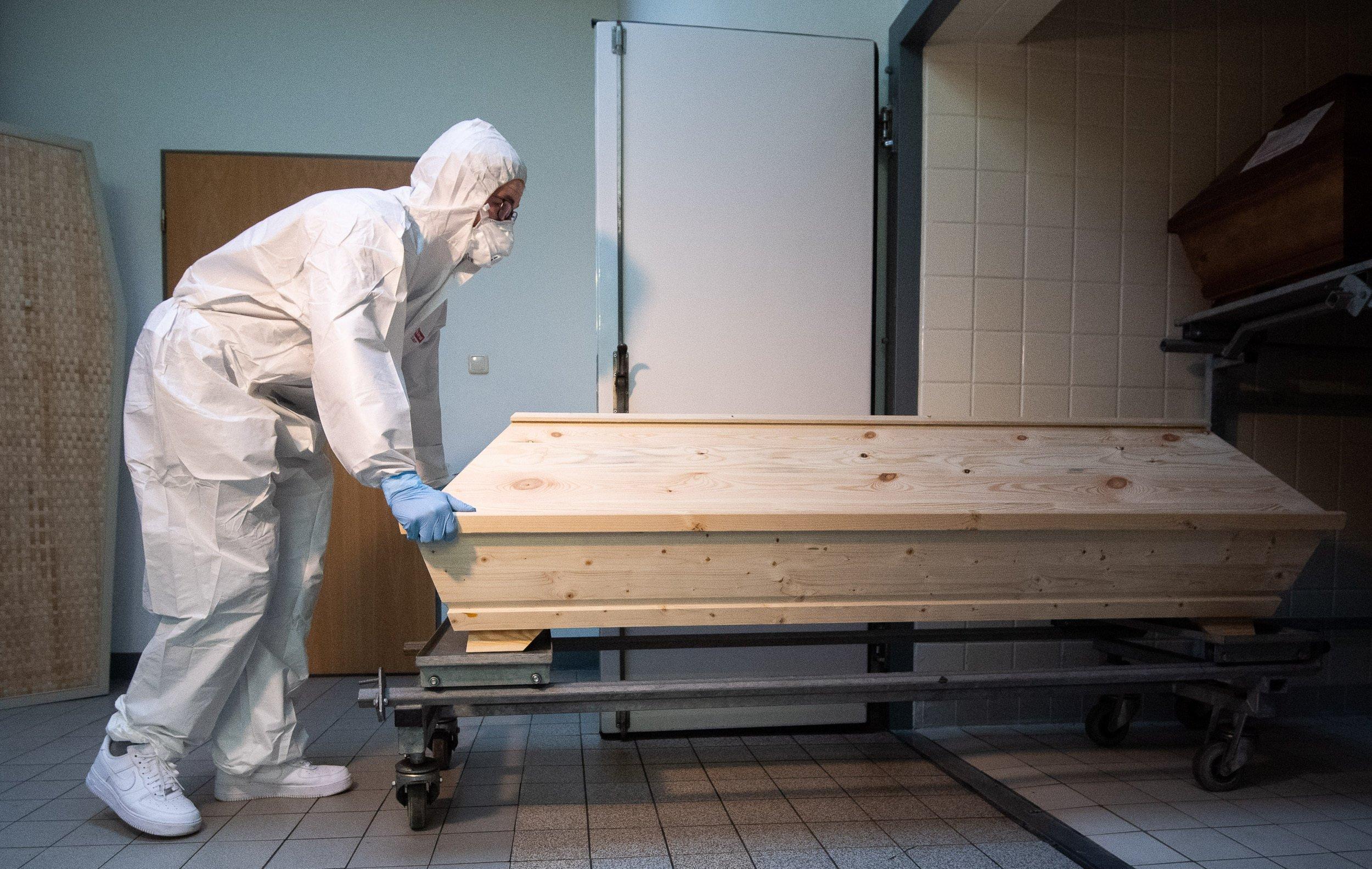 Ein Mann im Ganzkörperanzug, mit Gesichtsmaske und Handschuhen schiebt einen hellen Holzsarg auf einem Rollwagen in eine Kammer. Darin sind weitere Särge zu sehen.