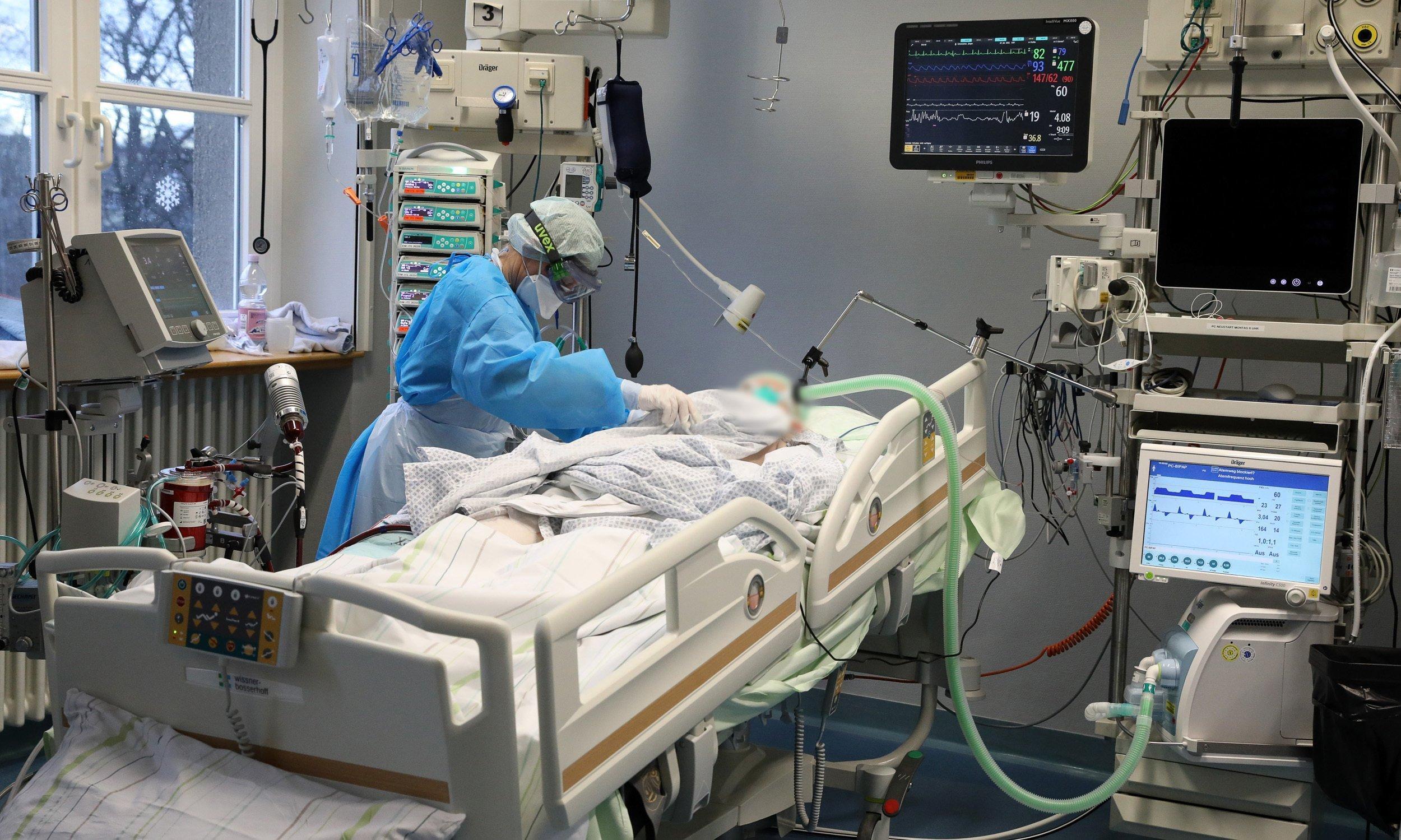Ein Krankenbett mit einem Patienten in weißem Hemdchen. Rundherum medizinische Geräte mit Bildschirmen. Eine Person in blauem Schutzanzug mit Schütze, Gesichtsmaske, Haube, Handschuhen und Skibrille beugt sich über den Patienten.