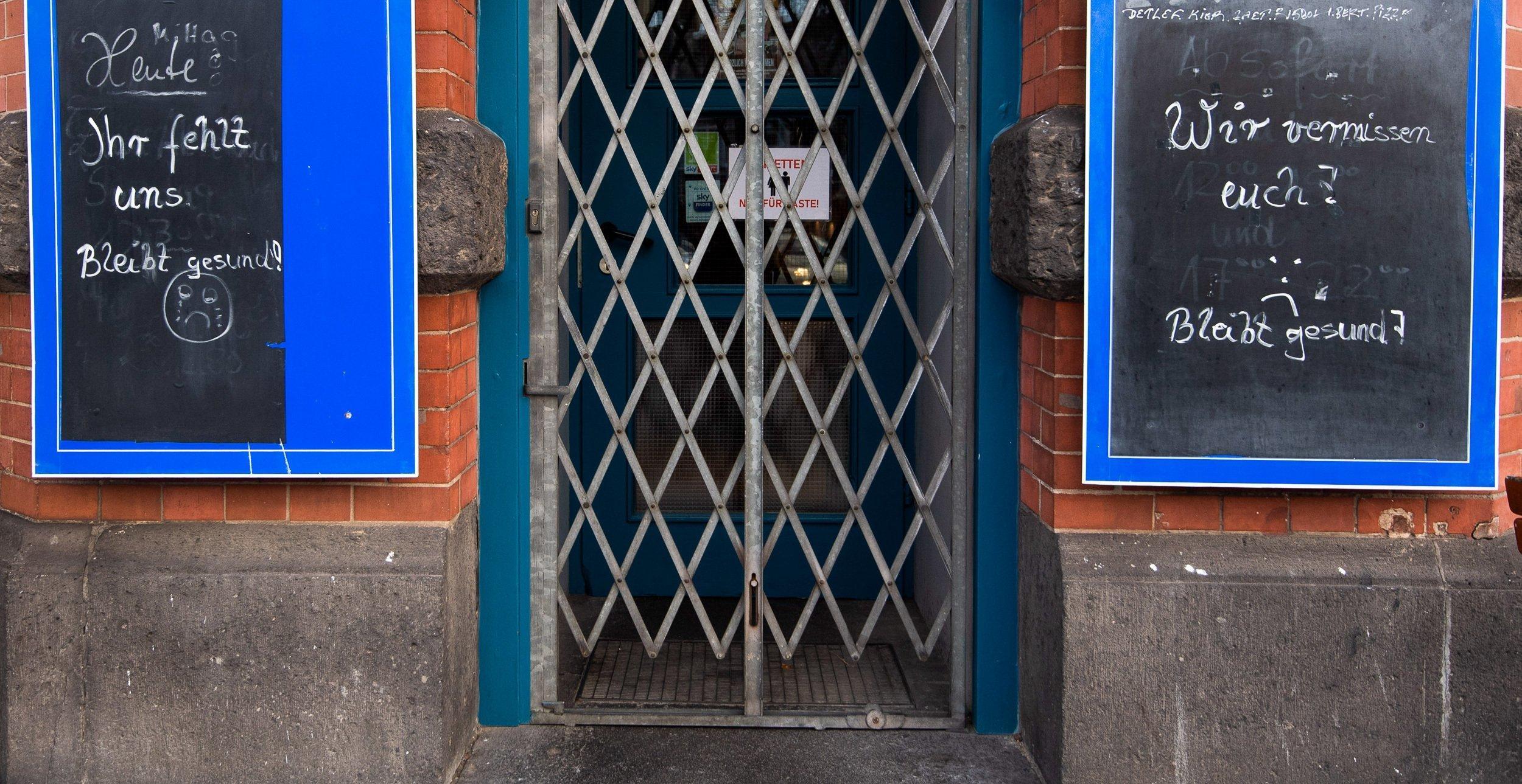 """""""Ihr fehlt uns. Bleibt gesund!"""" und """"Wir vermissen euch."""" – Zwei Tafeln neben der Tür einer Kneipe sind mit einem Gitter versperrt."""