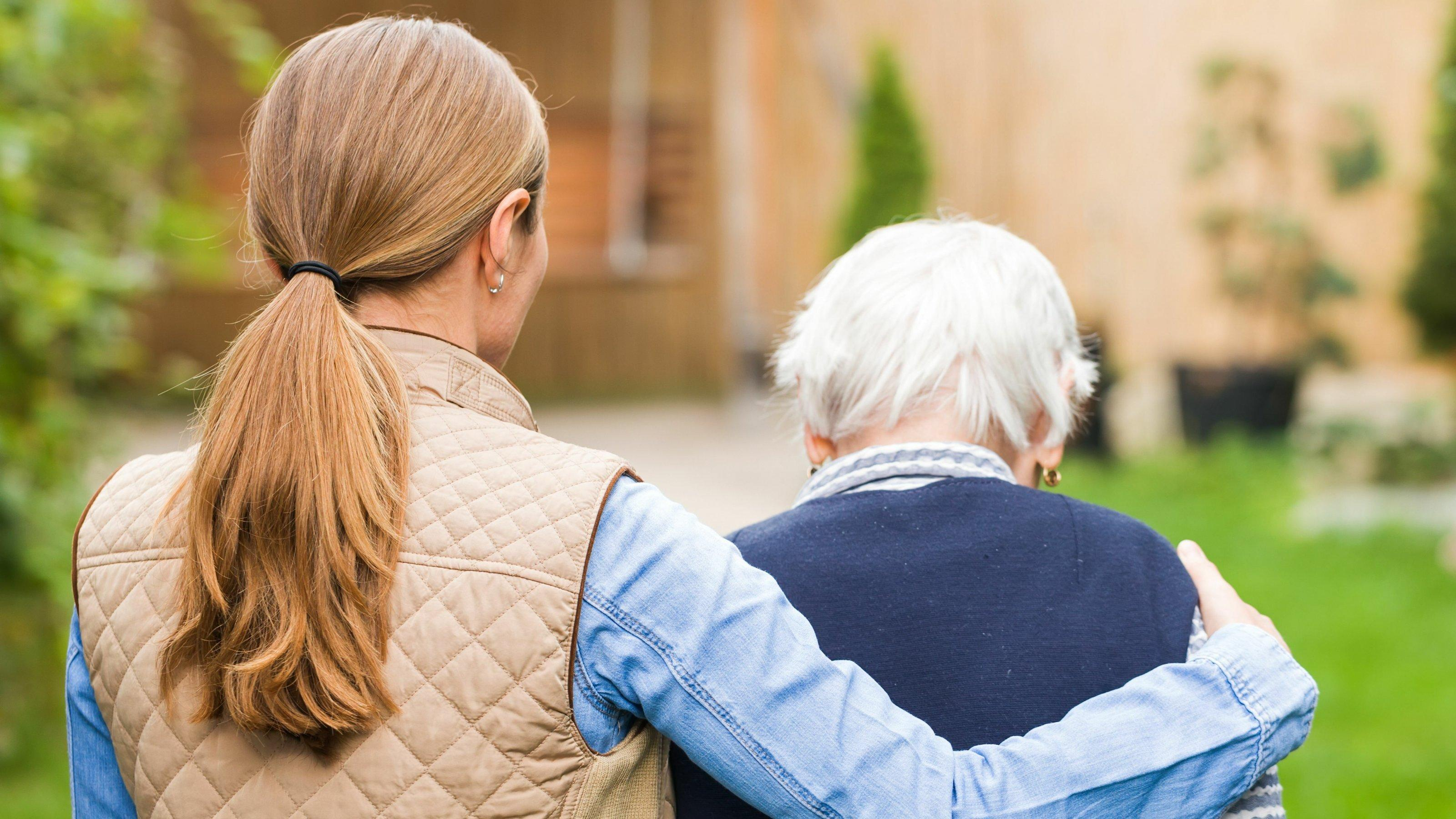 24-Stunden-Pflege: Eine ausländiche Pflegekraft hilft beim Spazierengehen. Hier führt eine Pflegerin eine alte Dame.