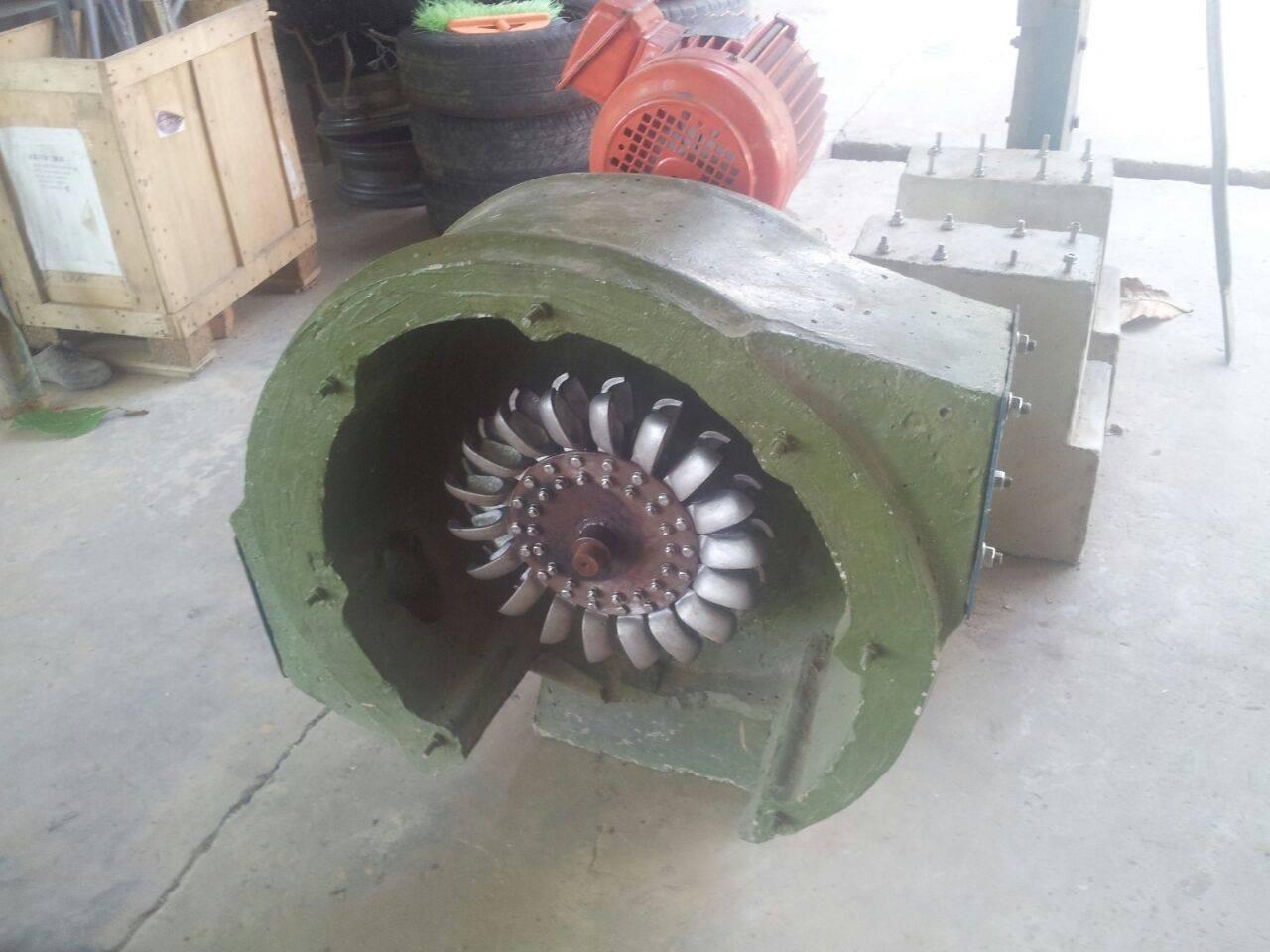 Das Foto zeigt ein Schaufelrad in einer grünlackierten Metallummantelung –  … Das Gehäuse der Turbine besteht manchmal auch aus Beton und wird erst vor Ort gegossen, damit die schweren Bleche nicht auch noch zu abgelegenen Dörfern transportiert werden müssen. …