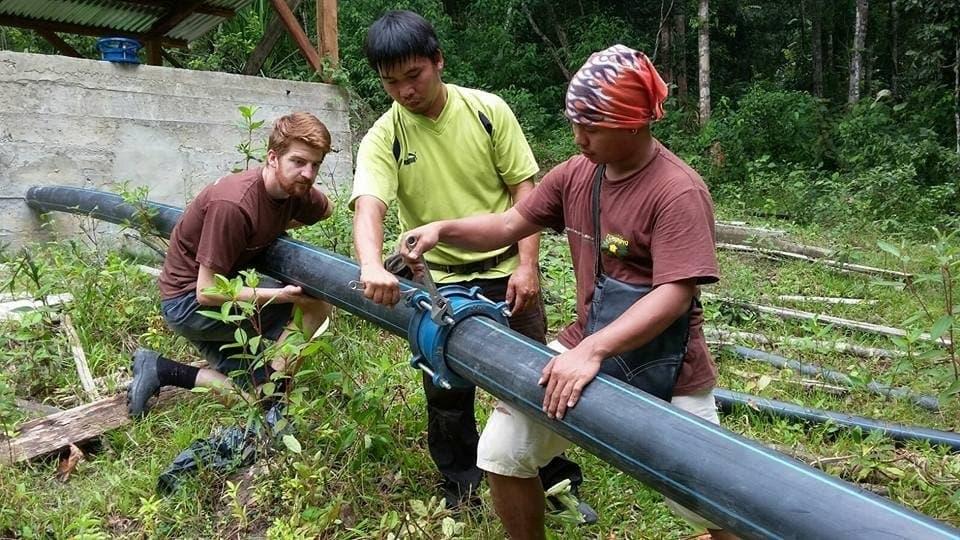 Das Foto zeigt drei Männer, die ein dickes schwarzes Wasserrohr verlegen. –  … Am Ort werden dann dicke Plastikrohre verlegt, durch die das Wasser zur Turbine strömt.Oft sind freiwillige Helfer aus westlichen Staaten dabei. …