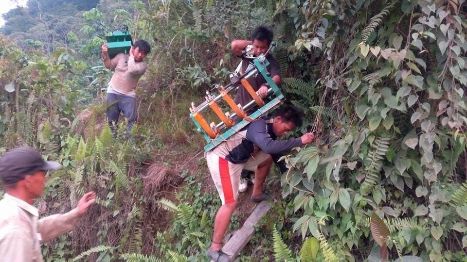 Das Foto zeigt mehrere Männer, die Maschinenteile auf dem Rücken über einen einfachen Pfad tragen und einen Anstieg mittels einer Leiter überwinden. –  … Oft genug müssen die Teile des neuen Wasserkraftwerks auf dem Rücken transportiert werden. …