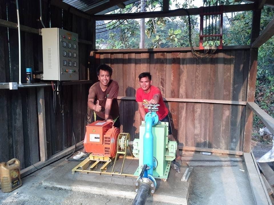 Das Foto zeigt zwei Männer, die hinter bunt lackierten Kästen in einer Holzhütte stehen und stolz lächeln. –  … Das fertige Kraftwerk …