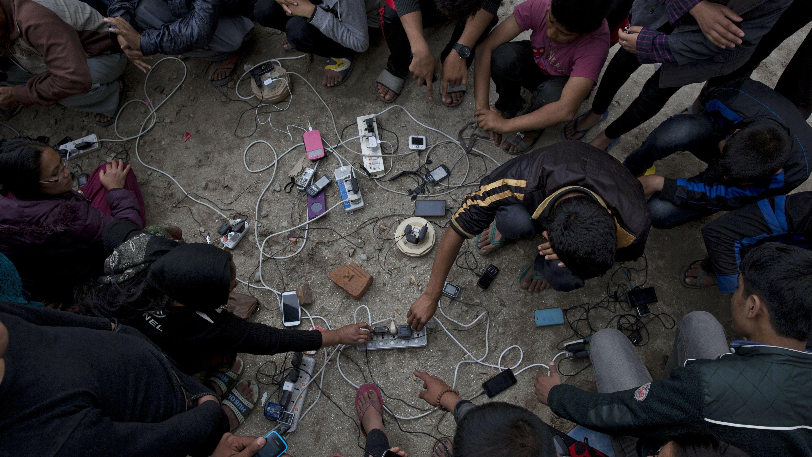 Nach einem Erdbeben im April 2015luden Dorfbewohner ihre Mobiltelefone auf einer Freifläche in Kathmandu, Nepal. Sie suchten in der erdbebengeschädigten Stadt nach ihren verlorenen Angehörigen. Das Bild zeigt mehrere Menschen um Handys, die an mehreren Steckern geladen werden.