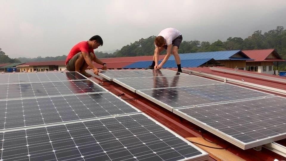Das Foto zeigt zwei Männer, die Solarzellen auf einem Dach installieren. – … In manchen Dörfern baut die Firma auch ein Netz auf, in dem das Wasserkraftwerk in der Regenzeit und Solarzellen in der Trockenzeit den Strom liefern. …