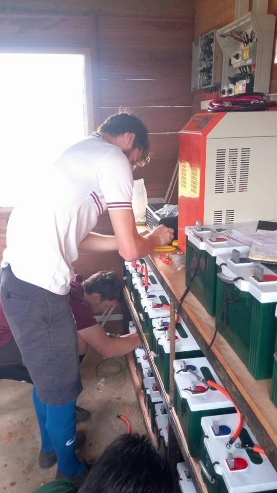 Das Foto zeigt einen Mann, der Batterien in der Größe von Autobatterien mit Kabeln verbindet. – … Batterien speichern dann den Strom, damit auch nach Sonnenuntergang noch Energie da ist.