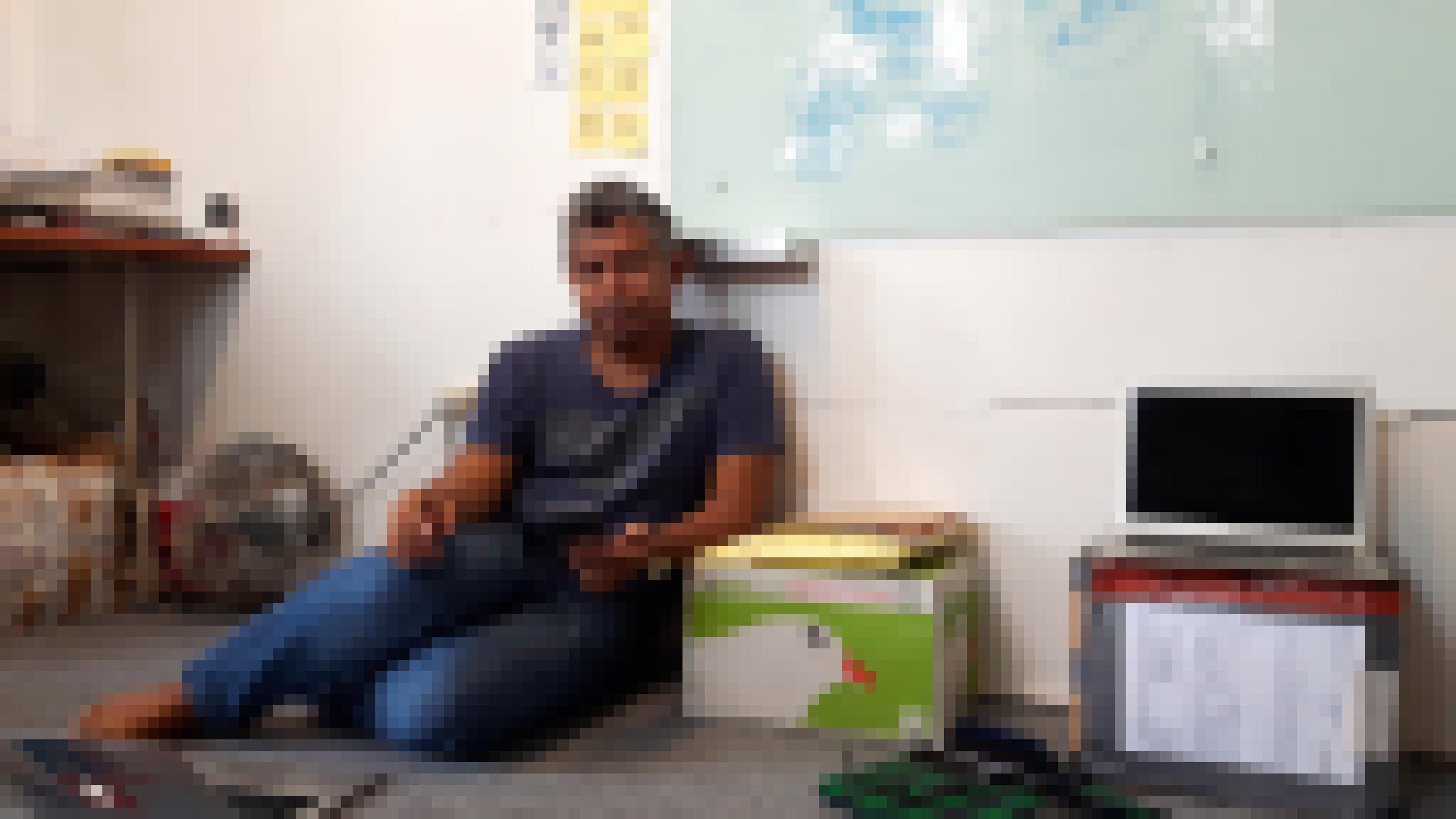 Ade Darmawan sitzt barfuß auf dem Boden des Gemeinschaftsbüros von ruangrupa in Jakarta