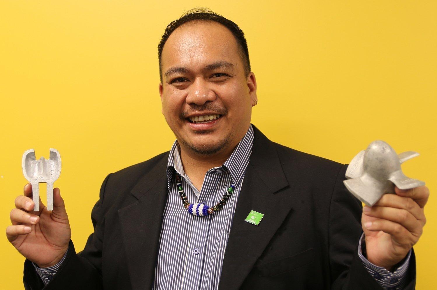 Ein Mann im Blazer mit gestreiftem Hemd hält Metallteile in der Hand und lächelt in die Kamera. –  Der Tonibung-Chef Adrian Lasimbang mit zwei selbst aus alten Aluminum-Dosen gegossenen Teilen von Wasserturbinen.