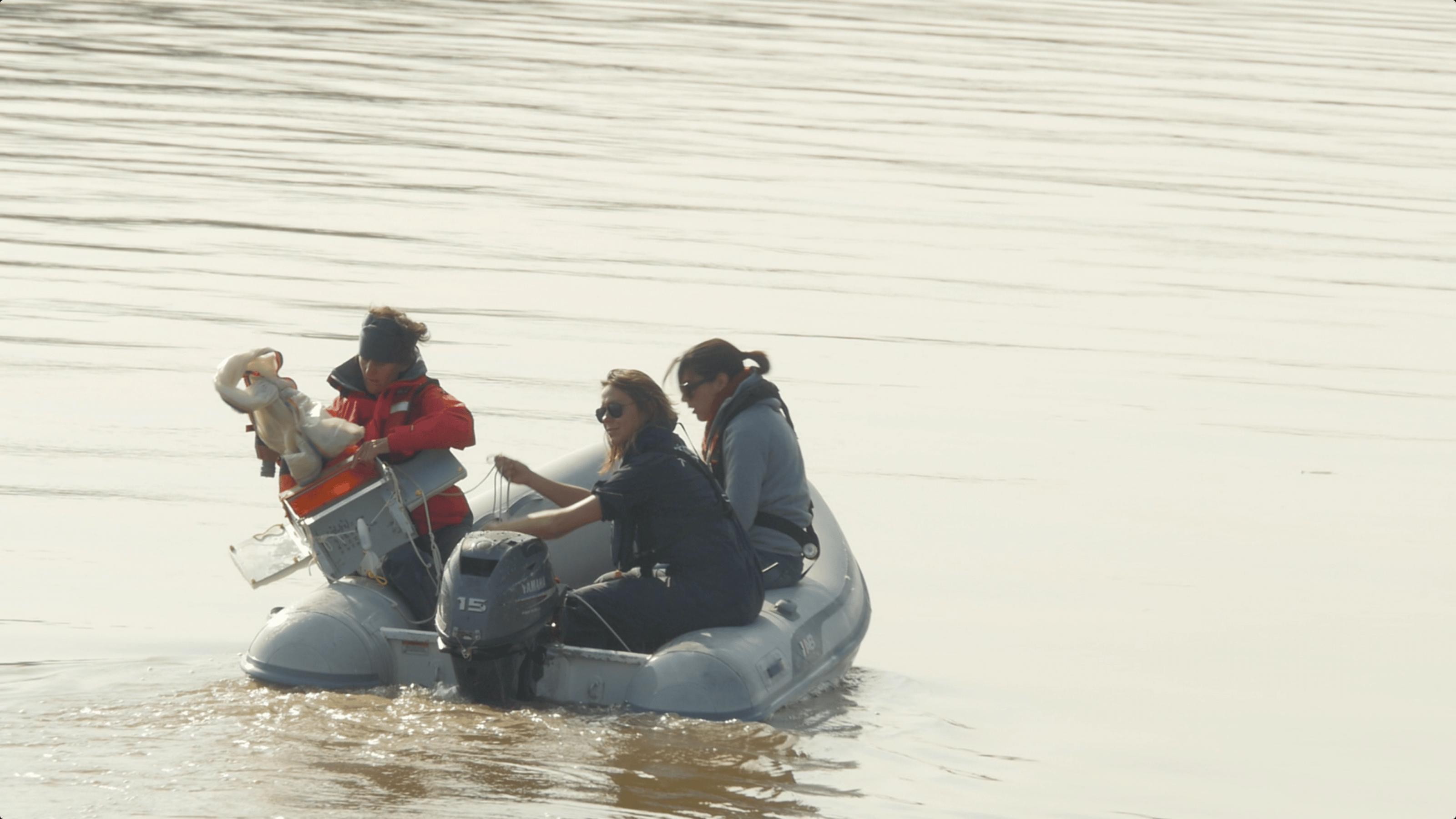 Einige Forscher fahren mit einem Boot auf dem Fluss Garonne und sammeln Proben.