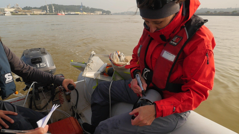 Die Wissenschaftlerin Alexandra ter Halle sitzt in roter Jacke auf dem Rand des Bootes und schaut nach unten. Sie hat einen Stift in der einen Hand und einen Behälter in der anderen Hand.