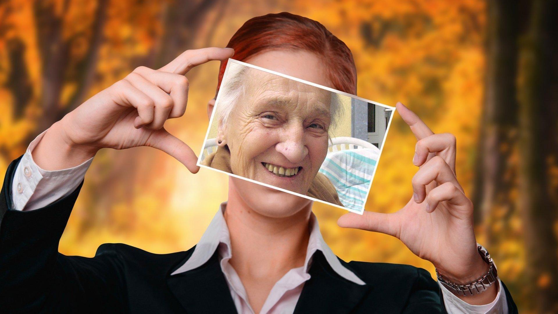 Junge Frau hält sich das Bild einer Alten vor ihr Gesicht