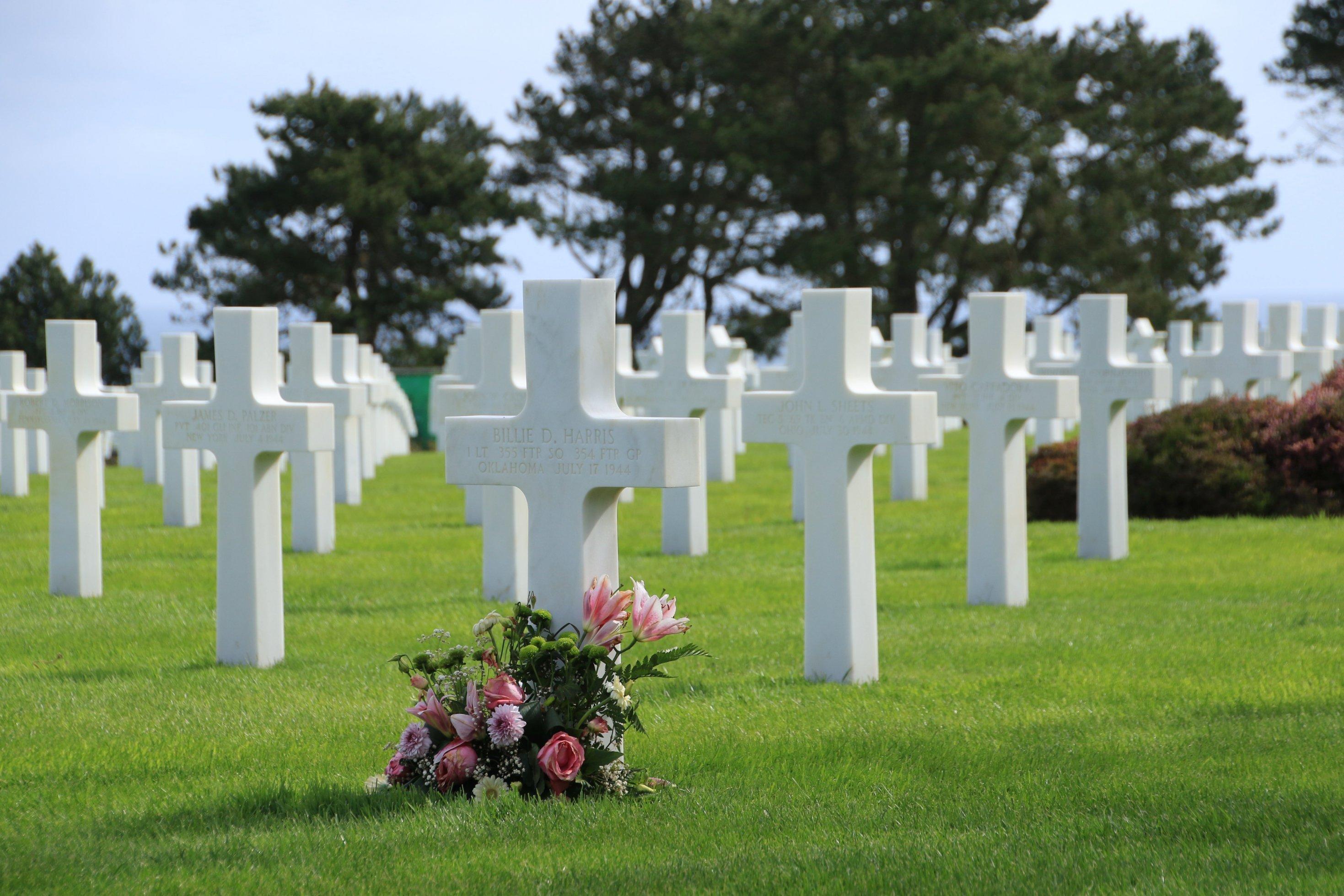 Weiße Kreuze stehen nebeneinander. Vor einem liegt ein Blumenstrauß.
