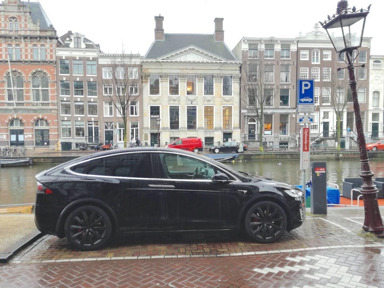 Ein schwarzes E-Auto steht auf einem Parkplatz an einer Ladestation.