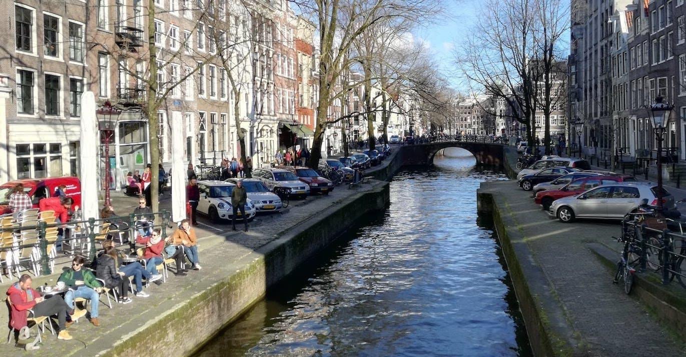 Blick von einer Brücke auf eine Gracht in Amsterdam, an der beidseitig Autos parken.