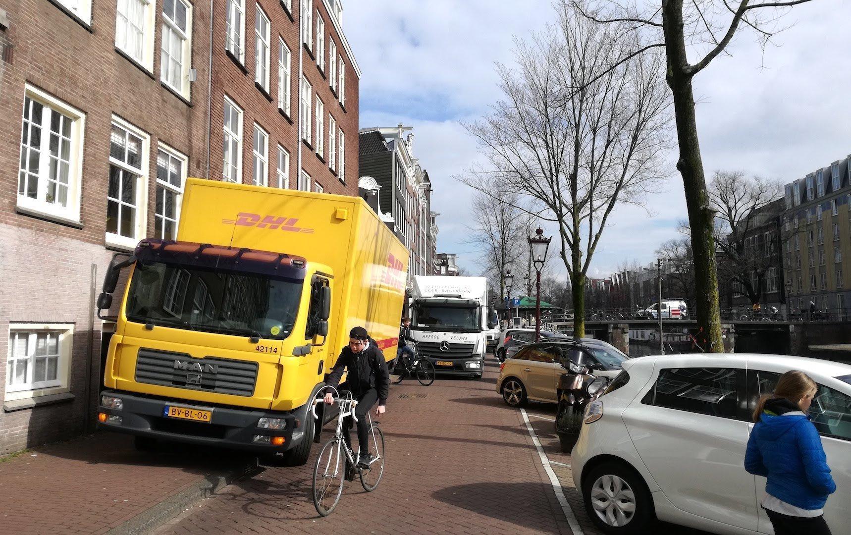 Zwischen Häusern und PKW-Parkplätzen stehen zwei LKW hintereinander halb auf Radwegen.