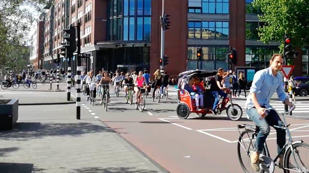 Ein Pulk Radfahrern und eine Rikscha queren eine Kreuzung in Amsterdam