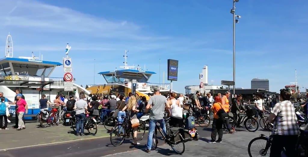 Hinter zahlreichen abgestiegenen Radfahrern sind Boote zu sehen.