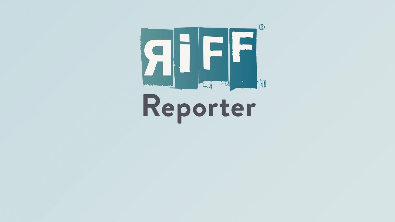 Radfahrer und Fußgänger gehen in Amsterdam über eine stark befahrene Kreuzung