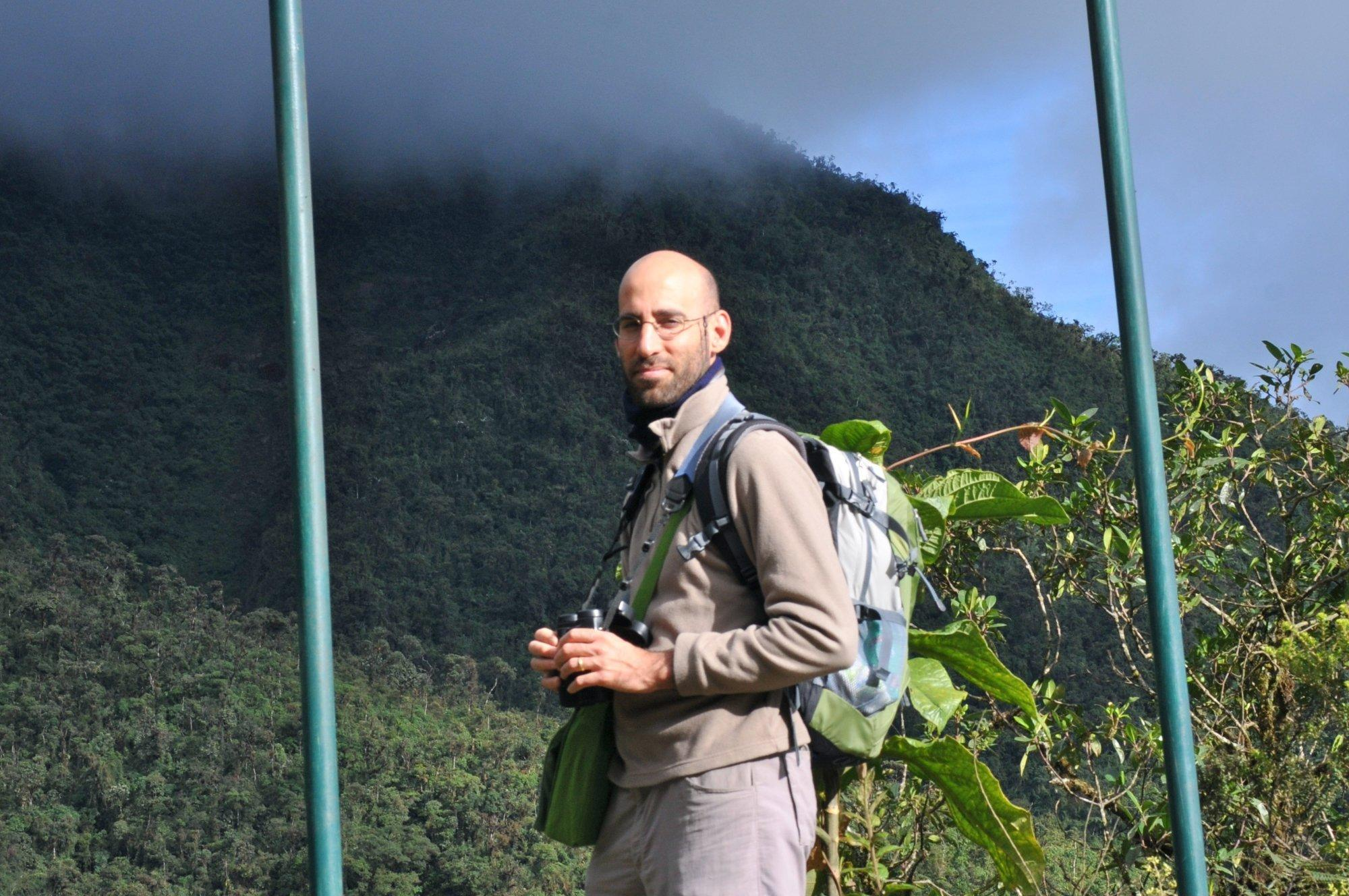 Ariel Brunner mit einem Fernglas in der Hand auf einer Wiese in Ecuador