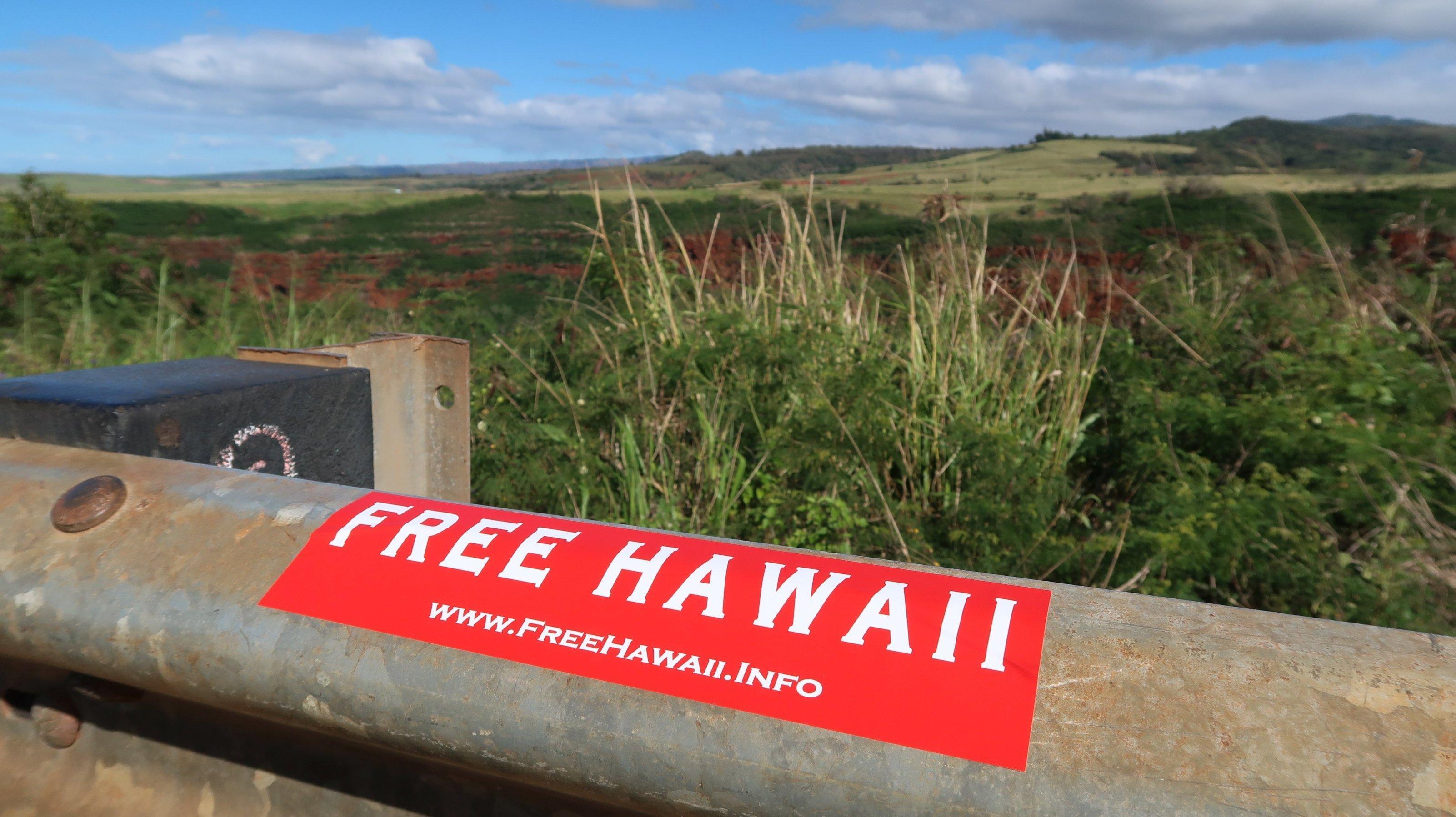 """Ein roter Aufkleber klebt auf einem Geländer mit der Aufschrift: """"Free Hawaii"""""""