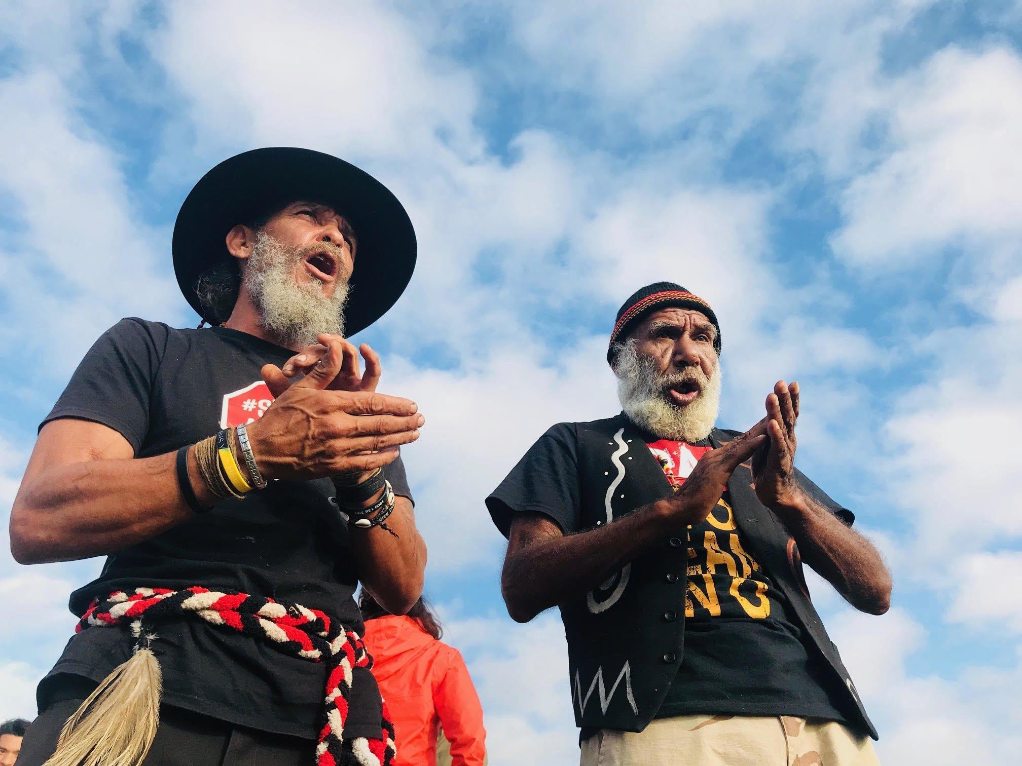 Zwei Männer, aufgenommen von schräg unten vor einem blauen, leicht bewölkten Himmel, klatschen in die Hände. Ihre Münder sind geöffnet so als ob sie singen. – Um zu verhindern, dass eine Kohlenmine ihre traditionellen Länder zerstört, und damit ihre Identität angreift, blockieren diese australischen Ureinwohner einer Eisenbahn-Linie.