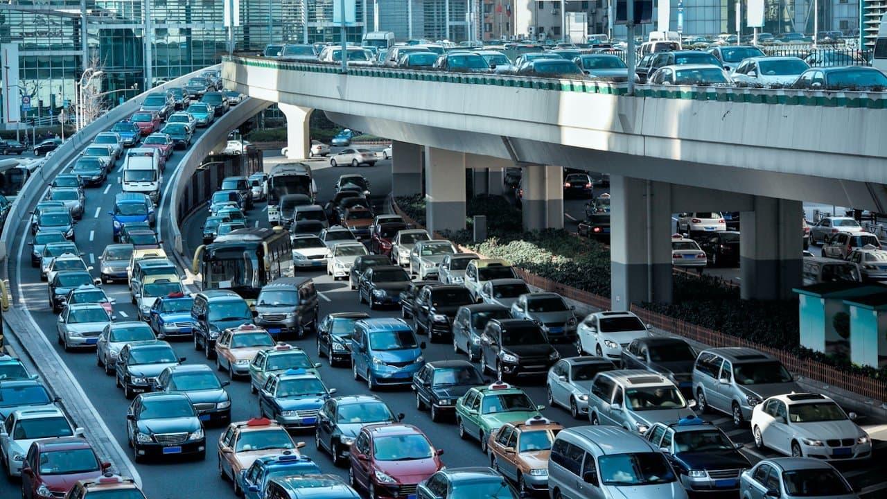 Auf der fünfspurigen Straße stauen sich die Autos  in beide Richtungen. Sie stehen dicht gedrängt: Stoßstange an Stoßstange