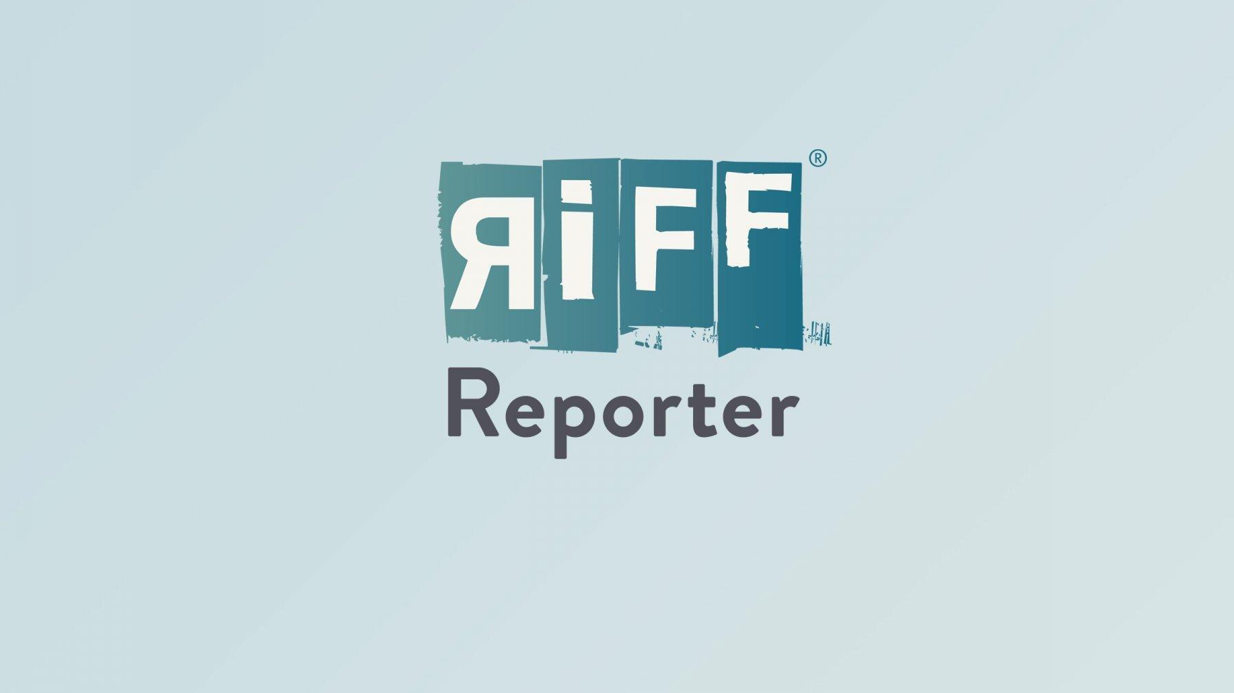 Links im Bild sieht man eine Filmkamera, hinter der unsere Autorin Ramona Seitz auf einem kleinen Hocker sitzt. Ihr Blick geht zu ihrem Interviewpartner Jude Thadaeus Ruwa'ichi, dem damaligen katholischen Erzbischof von Mwanza, Tansania, der ca. zehn Meter entfernt (im rechten Teil des Bildes) unter einem Baum sitzt. Er trägt ein weißes priesterliches Gewand. Ganz rechts im Bild steht mit dem Rücken zum Betrachter eine Frau, die für das Interview das an einer Stange befestigte Mikro hält.