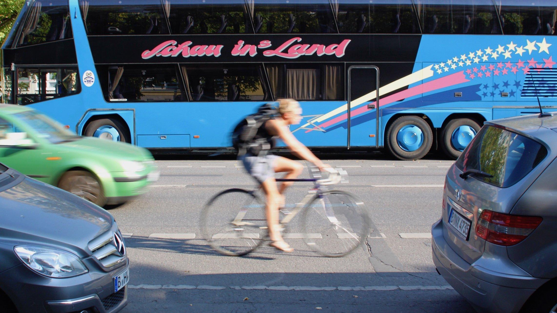 Es ist Sommer. Das Bild zeigt, die leicht verschwommen Seitenansicht einer Radfahrerin, die in T-Shirt und kurzer Hose auf einem blau-weißen Rennrad über die Straße fährt. Auf der gegenüberliegenden Seite parkt ein Bus mit der Aufschrift: Schau ins Land.
