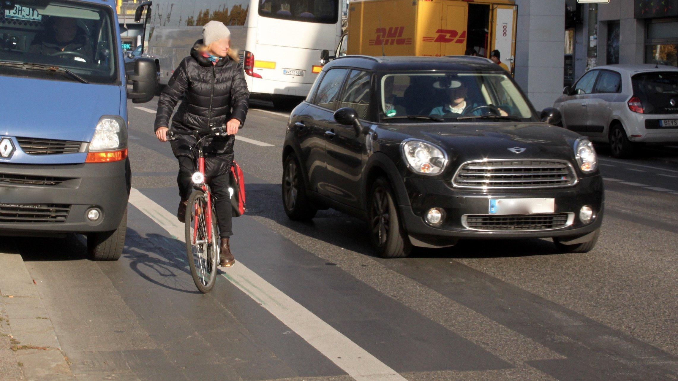 Eine Radfahrerin hat einen blauen Transporter überholt, der ihren Radweg auf der Straße blockiert. Der Verkehr ist dicht. Direkt links von ihr fährt ein Mini.