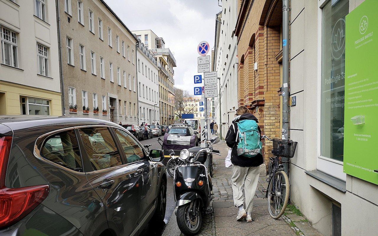 An der Hauswand rechts parkt ein Fahrrad, am linken Bordsteinrand ein Motorroller. Eine Frau geht durch die schmale Lücke