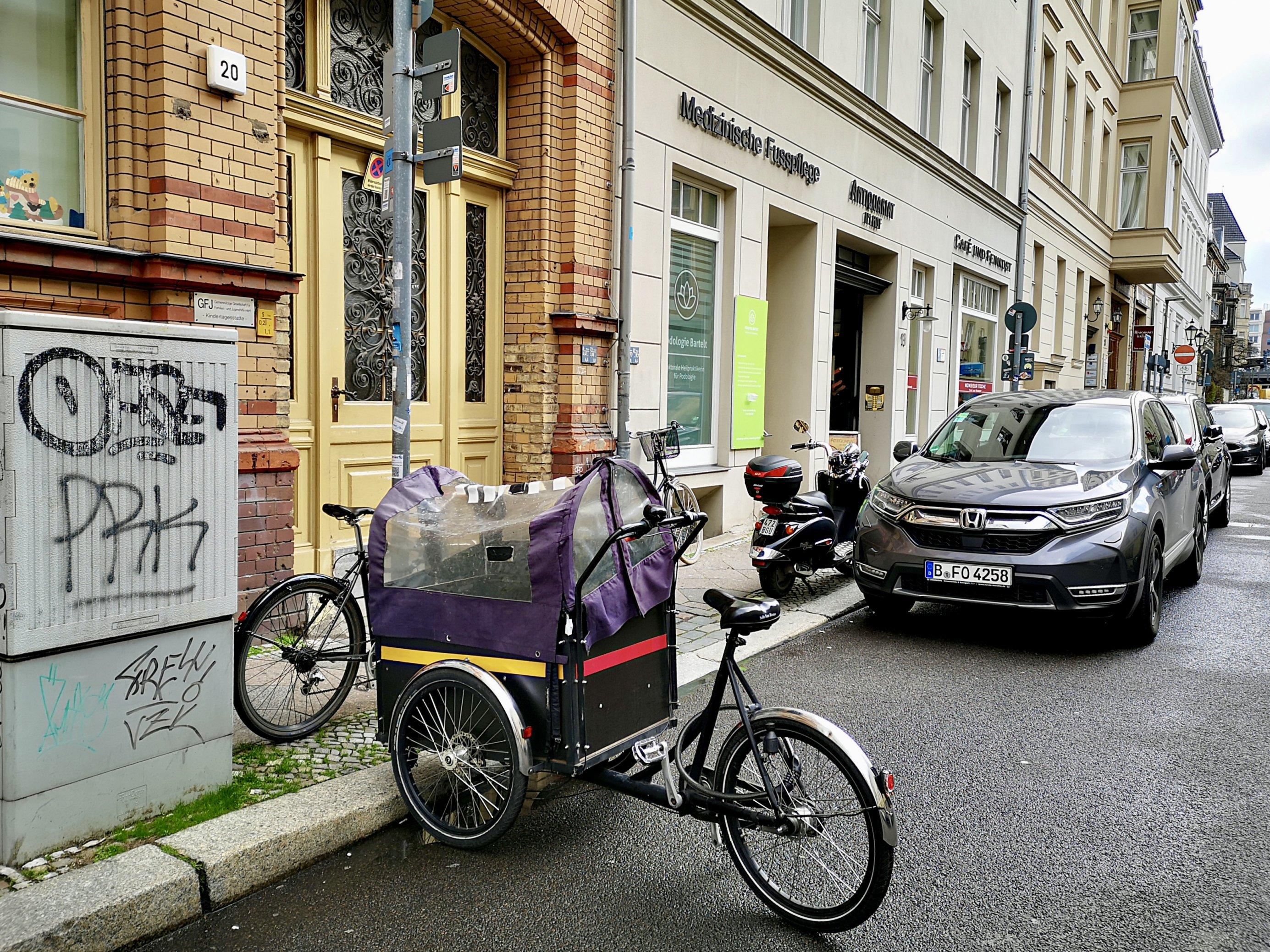 Das Lastenrad parkt auf der Straße. Die Transportbox steht mit der Kopfseite am Bordstein