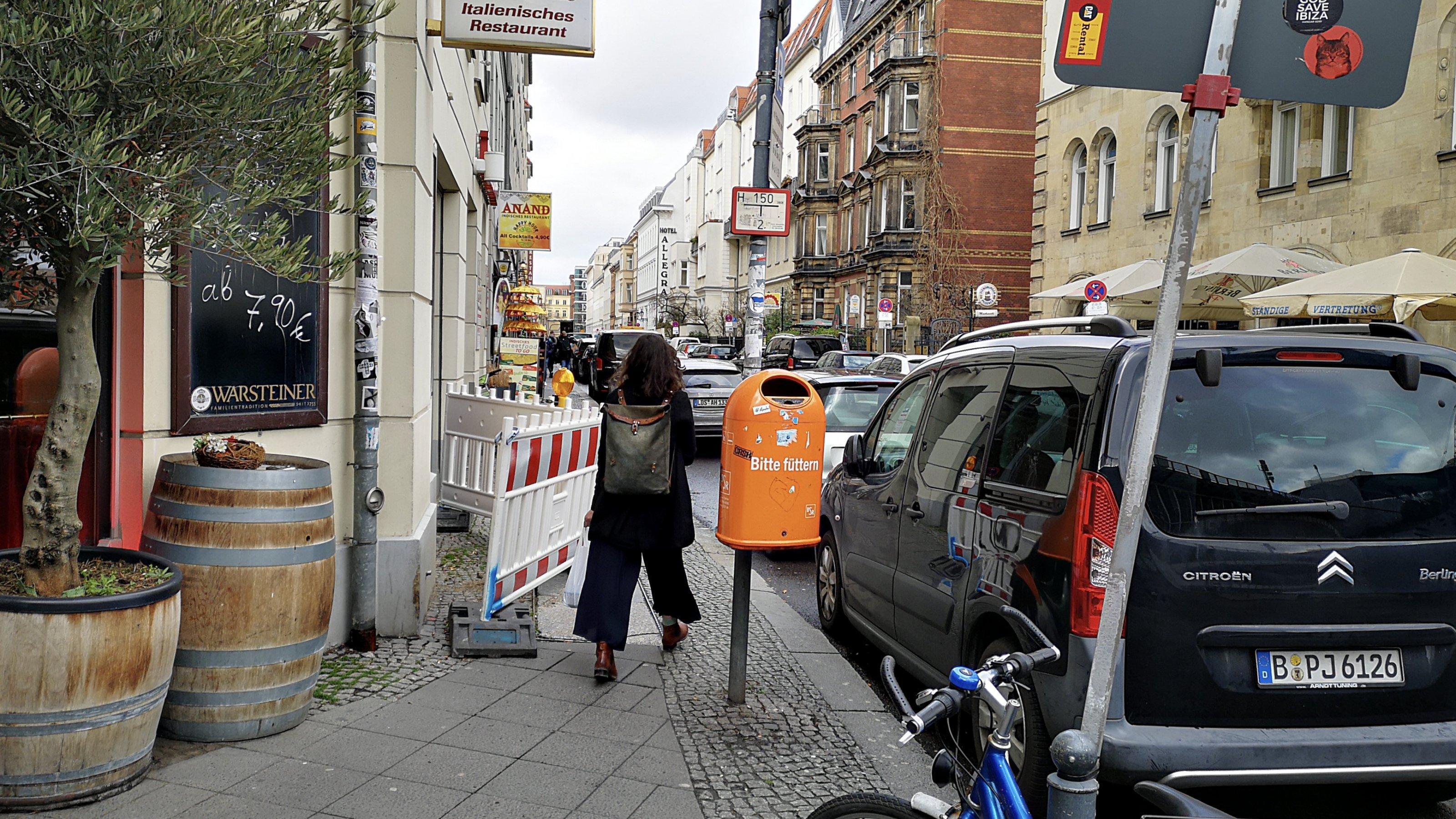 Eine Absperrung versperrt die Hälfte des Gehwegs. Die Frau, die auf Fußweg sieht man von hinten. Sie trägt einen Rucksack.