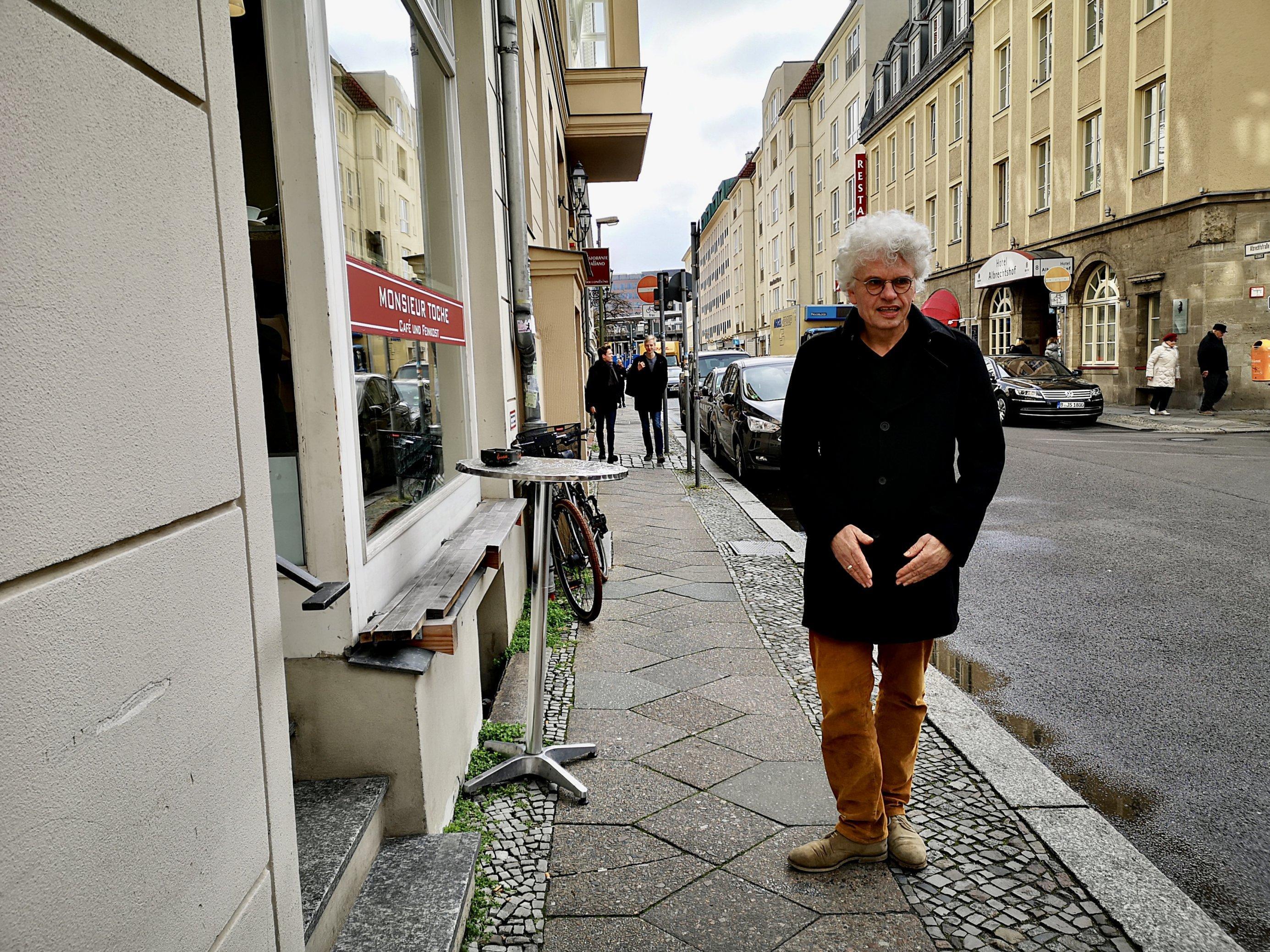 Links vor dem Café steht ein Bistrotisch an der Wand. Roland Stimpel steht am rechten Rand des Gehwegs und blickt in die Kamera